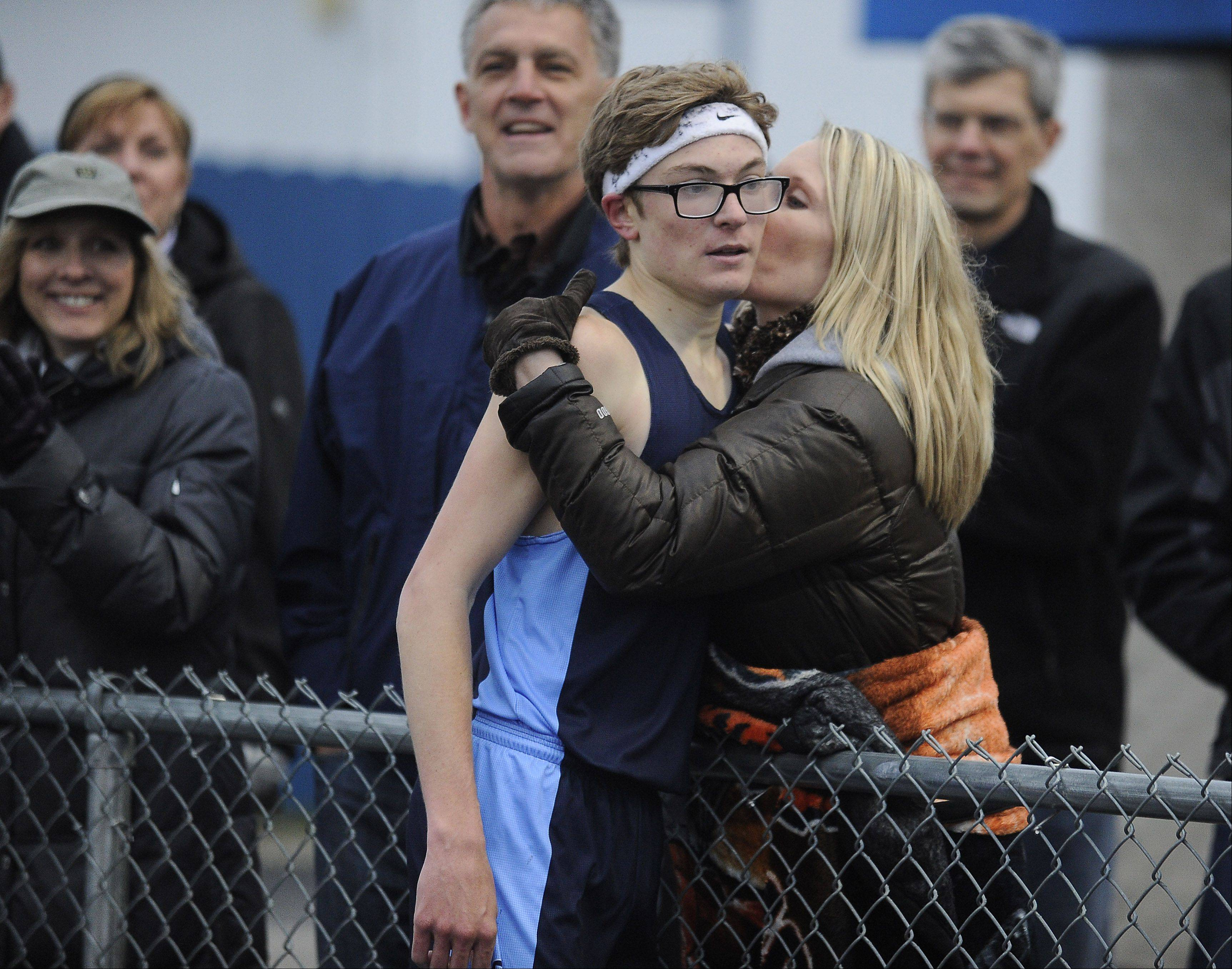 Mark Welsh/mwelsh@dailyherald.comQuentin Schaeffer of Prospect wins the 3,200-meter run and gets a kiss from his mom, Shannon, in the Mid-Suburban League meet at Hoffman Estates on Friday.