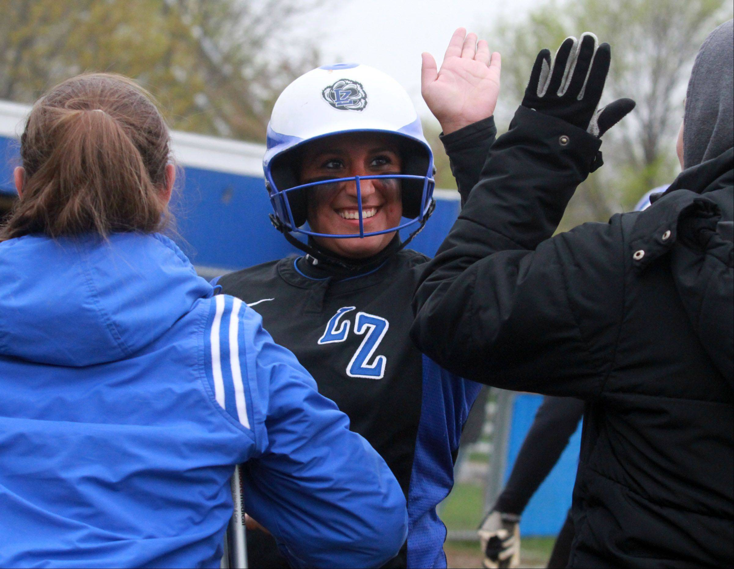 Lake Zurich's Carlee Parsons gets high-fives as she crosses home-plate after hitting a homer against Warren in Gurnee on Friday.