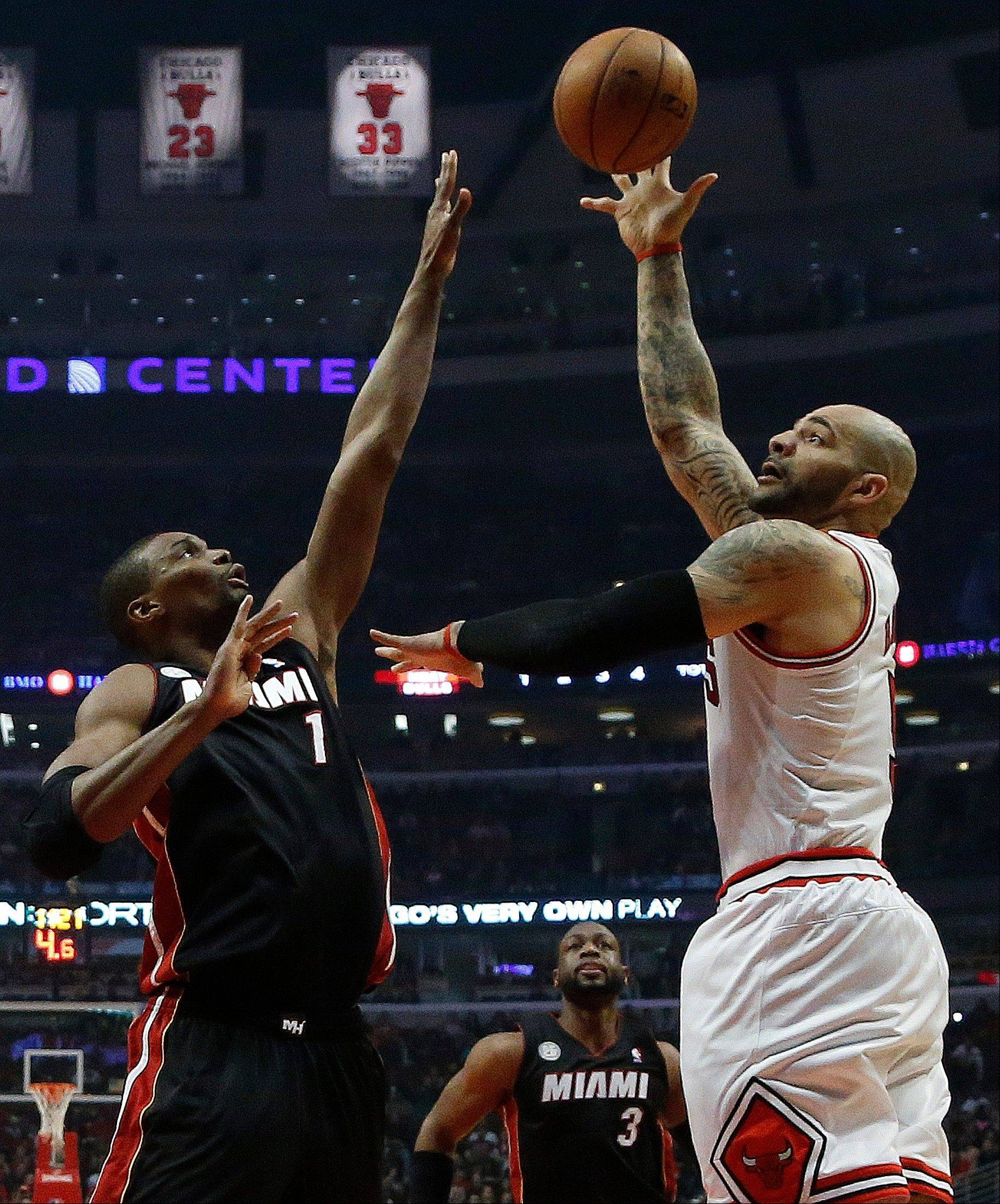 Chicago Bulls power forward Carlos Boozer (5) shoots over Miami Heat center Chris Bosh (1) during the first half of Game 3 of an NBA basketball playoffs Eastern Conference semifinal on Friday, May 10, 2013, in Chicago.