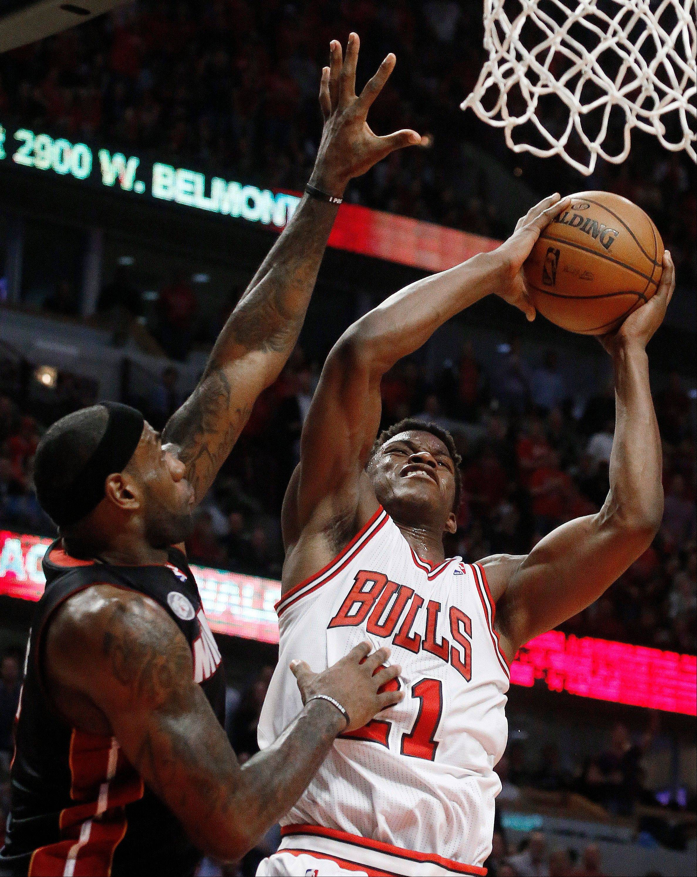 Chicago Bulls small forward Jimmy Butler (21) shoots against Miami Heat small forward LeBron James (6) during the second half of Game 3 of an NBA basketball playoffs Eastern Conference semifinal on Friday, May 10, 2013, in Chicago.