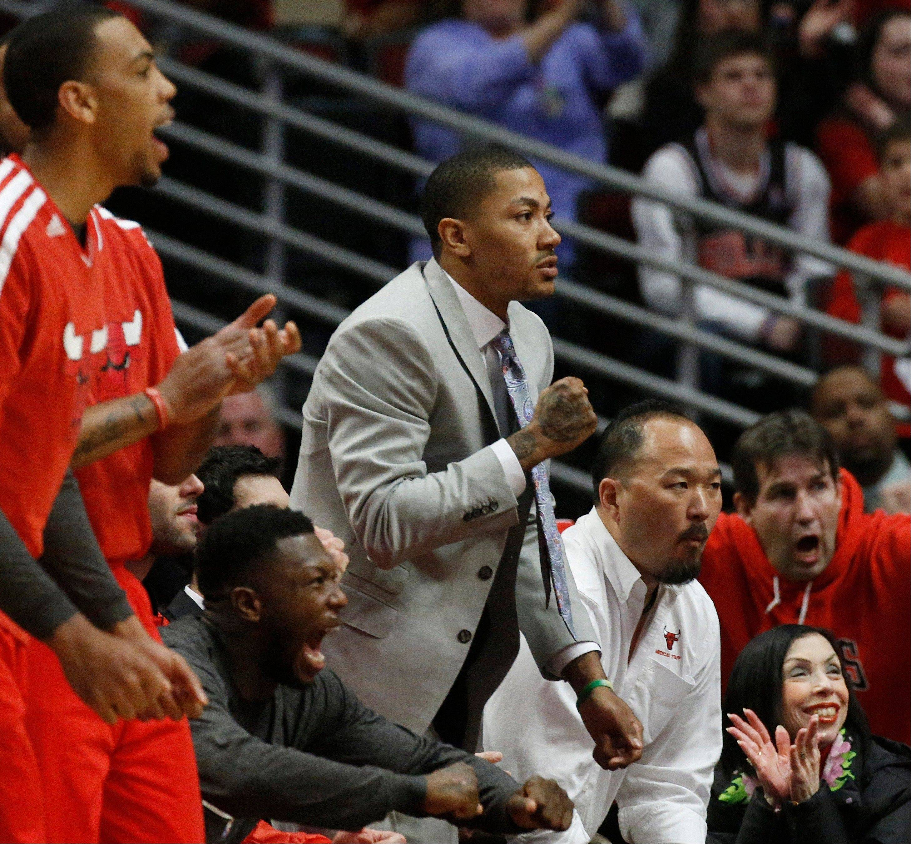 Chicago Bulls' Derrick Rose, in suit at center, cheers the team during the first half of Game 3 of an NBA basketball playoffs Eastern Conference semifinal against the Miami Heat on Friday, May 10, 2013, in Chicago.