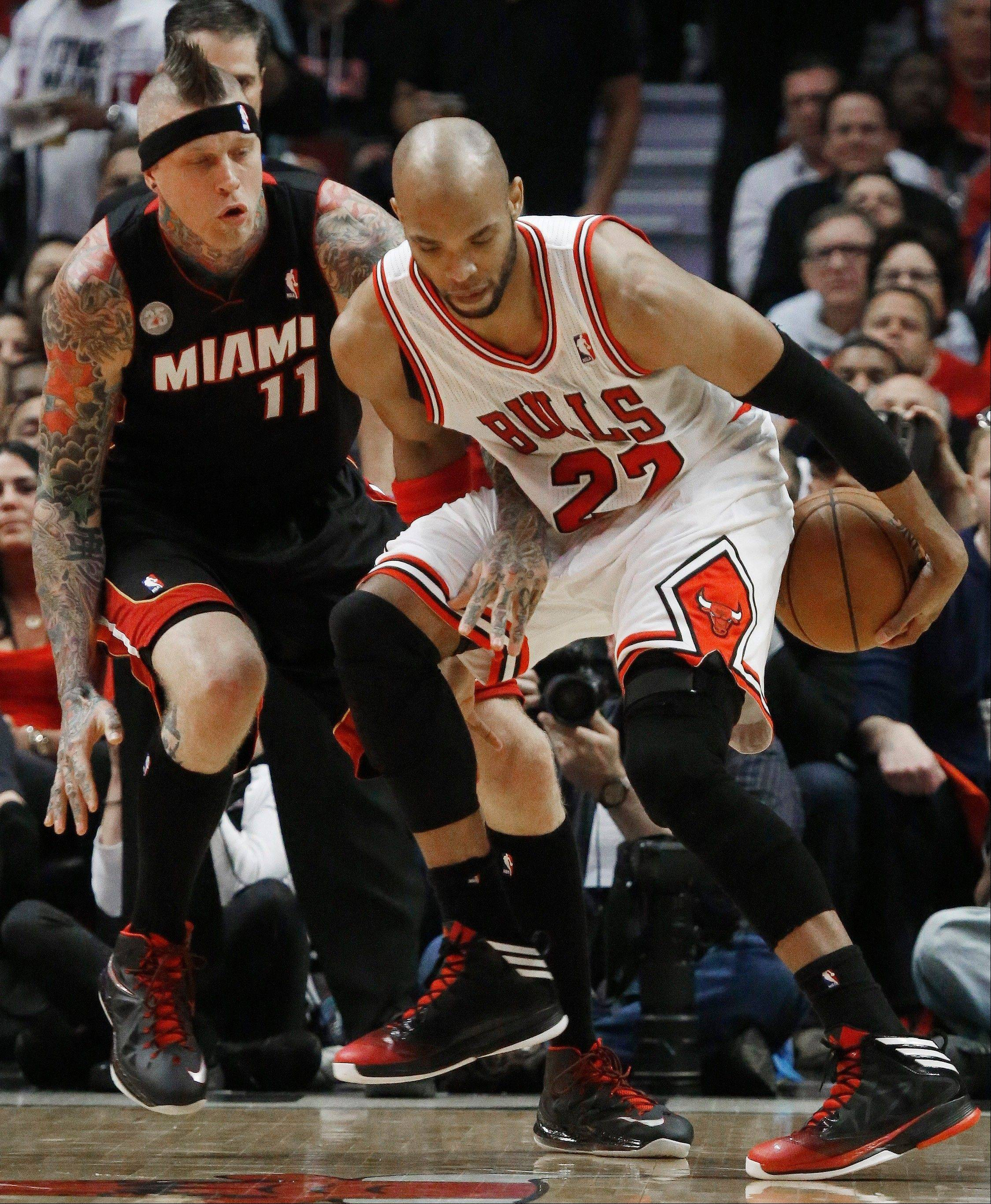 Chicago Bulls power forward Taj Gibson (22) tries to keep a loose ball as Miami Heat power forward Chris Andersen (11) looks on during the first half of Game 3 of an NBA basketball playoffs Eastern Conference semifinal on Friday, May 10, 2013, in Chicago.
