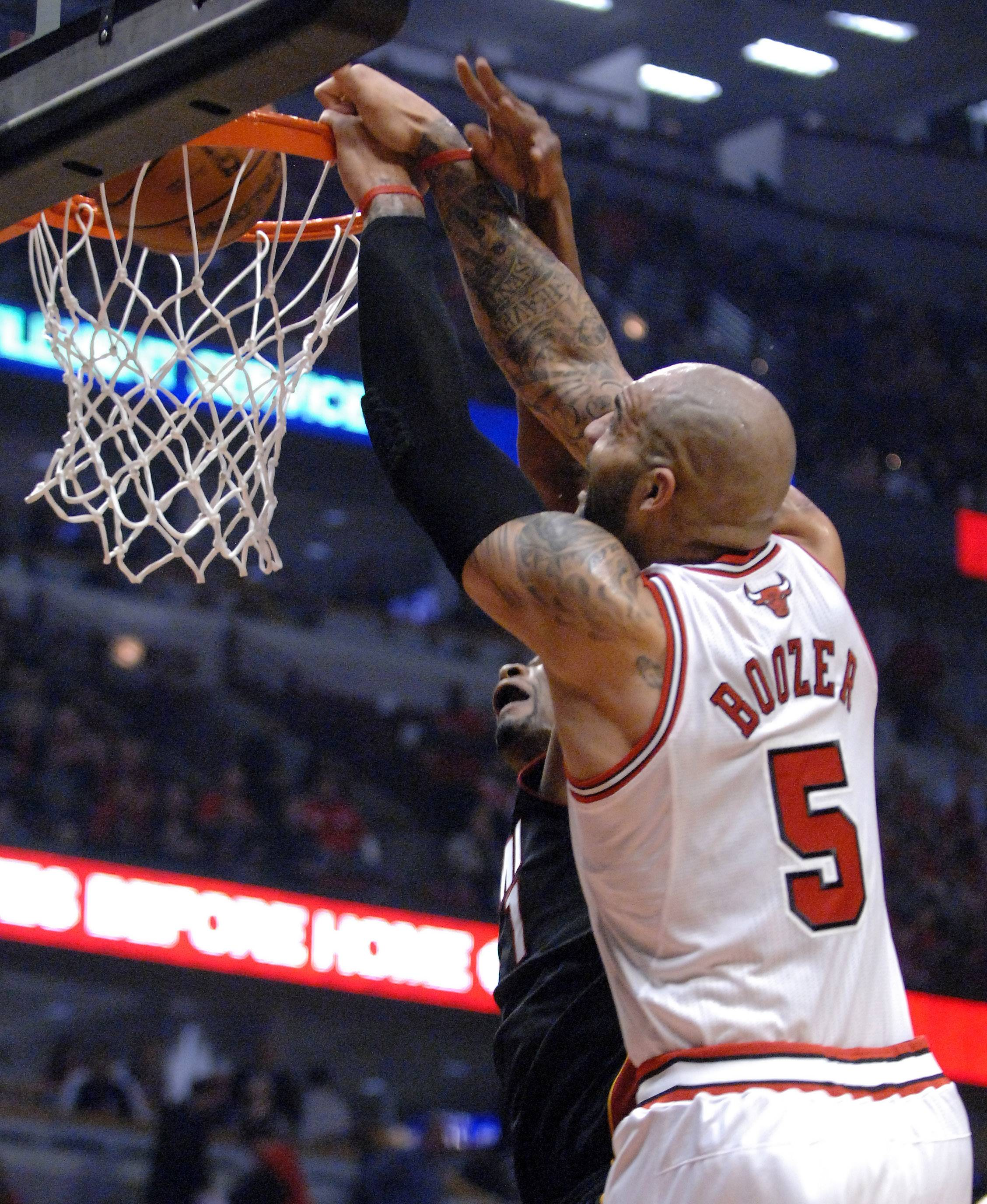 Chicago Bulls power forward Carlos Boozer (5) dunks over Miami Heat center Chris Bosh (1) during Game 3 of an NBA basketball playoffs Eastern Conference semifinal on Friday, May 10, 2013, in Chicago. The heat won 104-94.