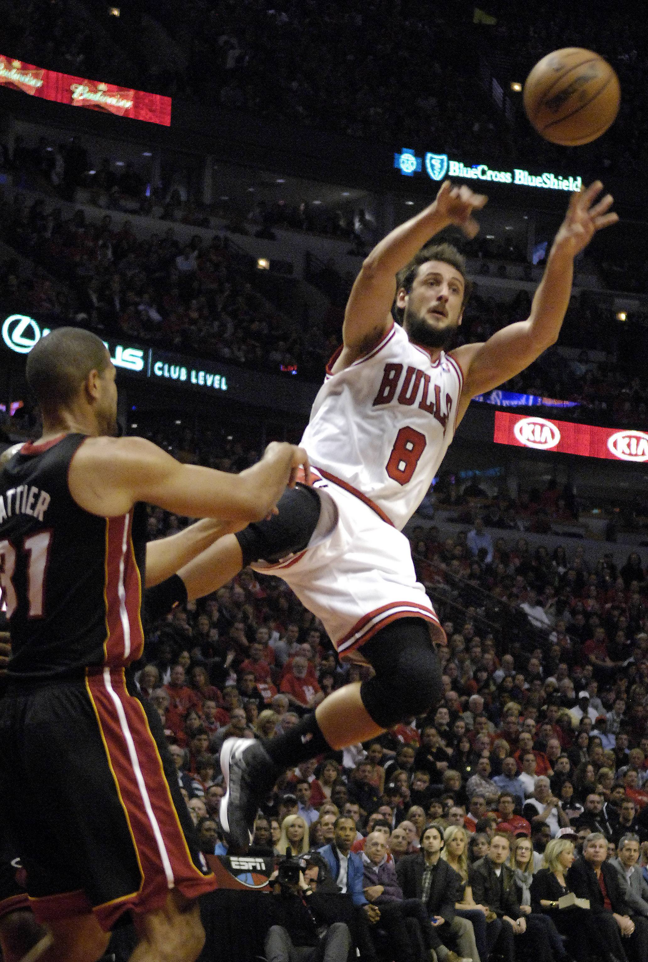 Chicago Bulls shooting guard Marco Belinelli (8) dishes out wide when his path to the basket gets blocked by Miami Heat small forward Shane Battier (31)  during Game 3 of an NBA basketball playoffs Eastern Conference semifinal on Friday, May 10, 2013, in Chicago. The heat won 104-94.