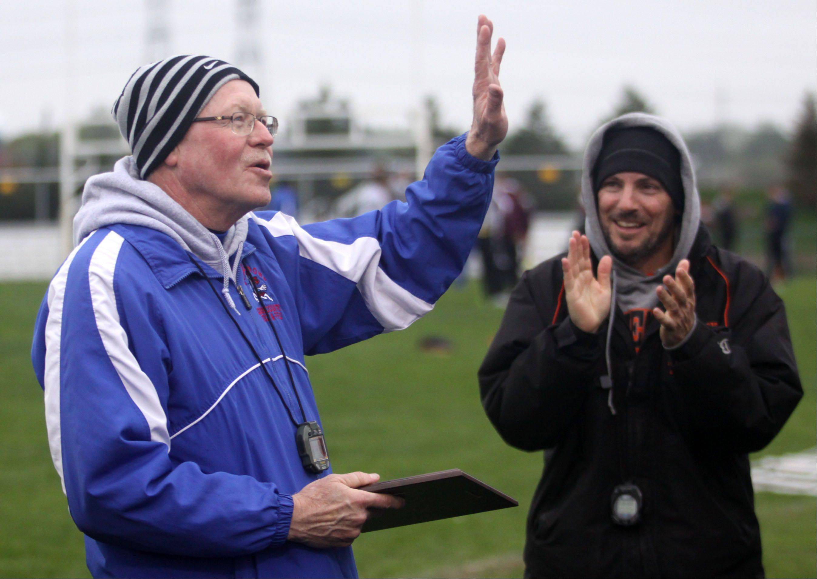 Longtime Dundee-Crown coach Tom Smith acknowledges the crowd as he is recognized for his many years of service during the Fox Valley Conference Boys Track & Field Championships at Al Bohrer Field on the campus of Cary-Grove High School Friday night. McHenry coach Dave D'Angelo, right, presented Smith with a plaque for the occasion.