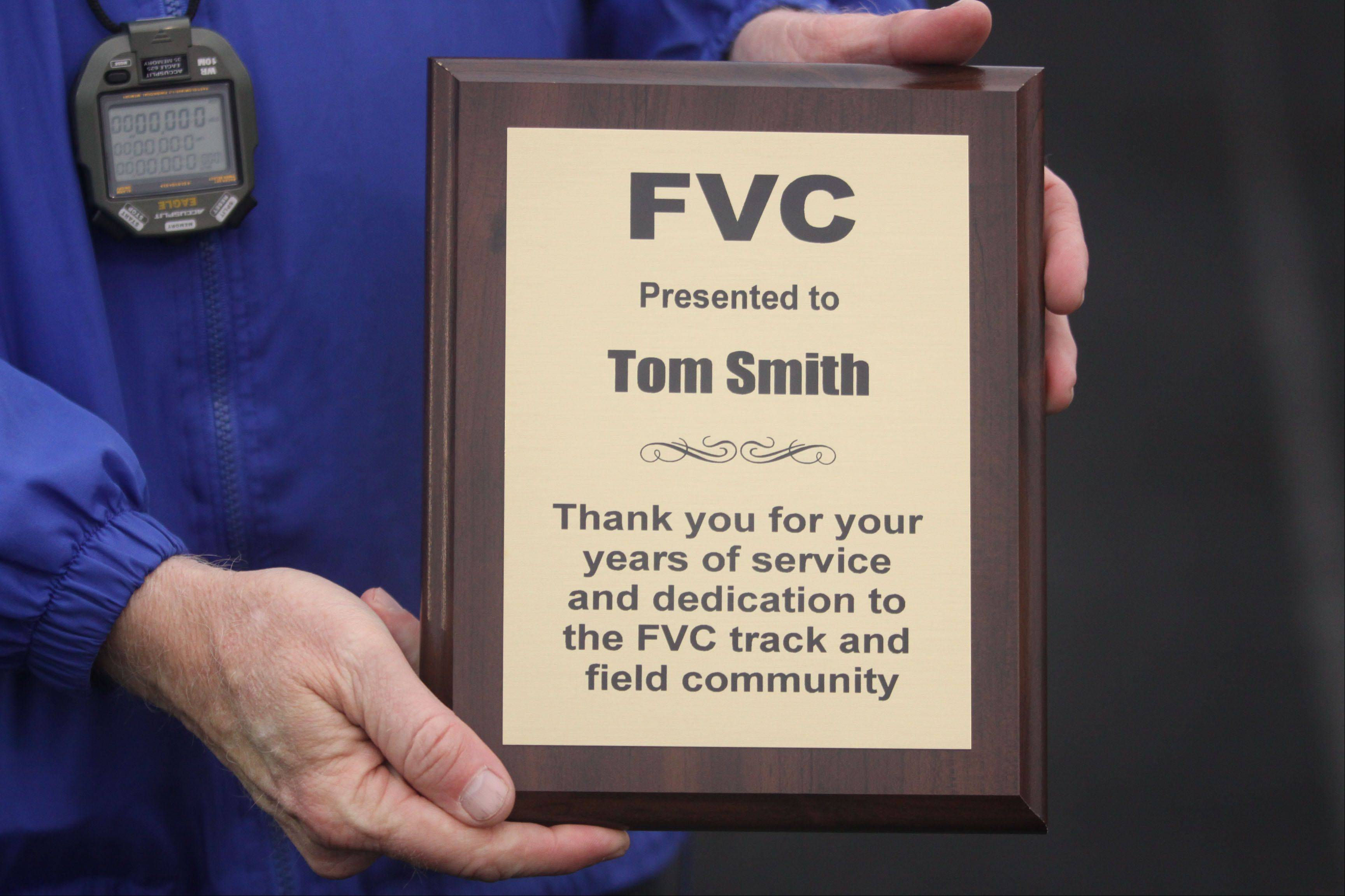 Longtime Dundee-Crown coach Tom Smith was recognized for his many years of service during the Fox Valley Conference Boys Track & Field Championships at Al Bohrer Field on the campus of Cary-Grove High School Friday night. McHenry coach Dave D'Angelo presented Smith with this plaque for the occasion.