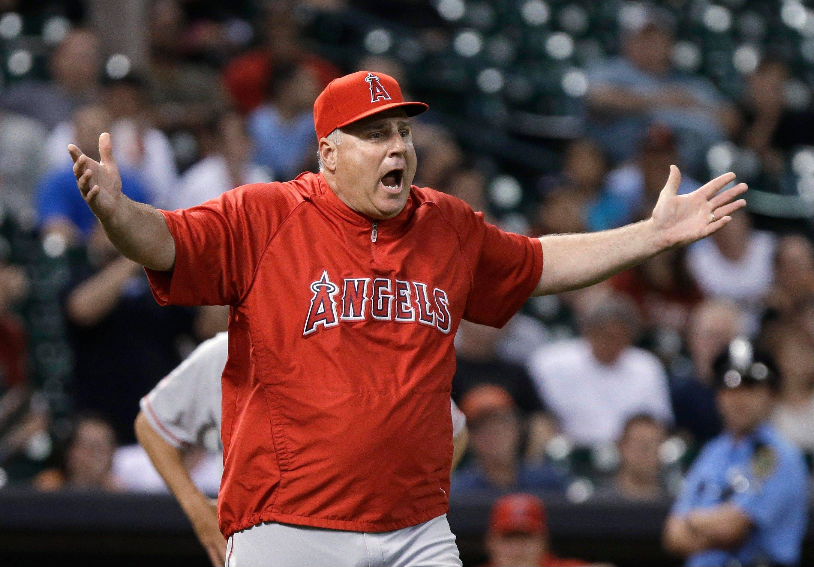 Los Angeles Angels manager Mike Scioscia questions the umpires on a Houston Astros pitching change in the seventh inning of a baseball game Thursday, May 9, 2013, in Houston.