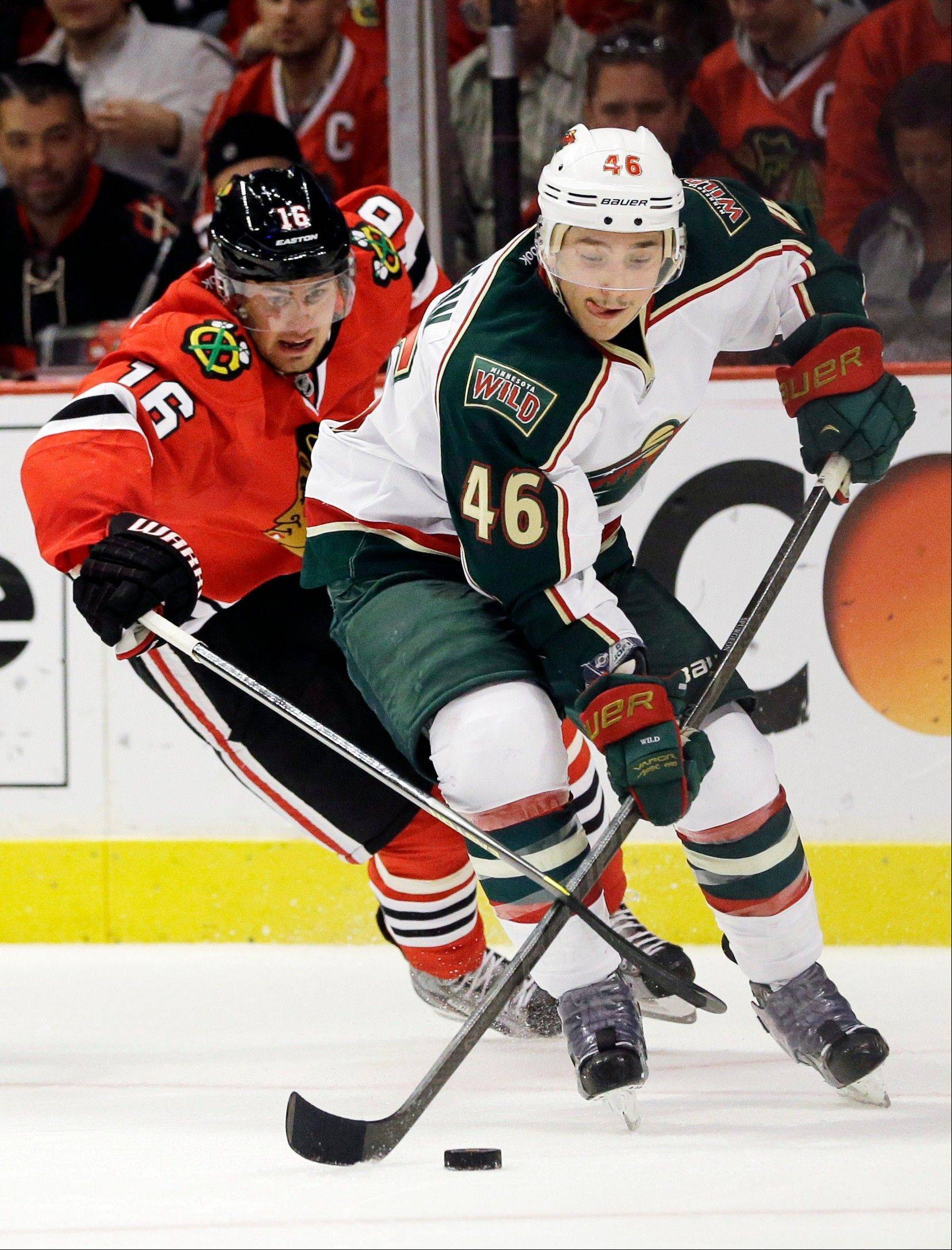 Chicago Blackhawks' Marcus Kruger (16) battles for the puck against Minnesota Wild's Jared Spurgeon (46) during the second period of Game 5 of an NHL hockey Stanley Cup first-round playoff series in Chicago, Thursday, May 9, 2013.