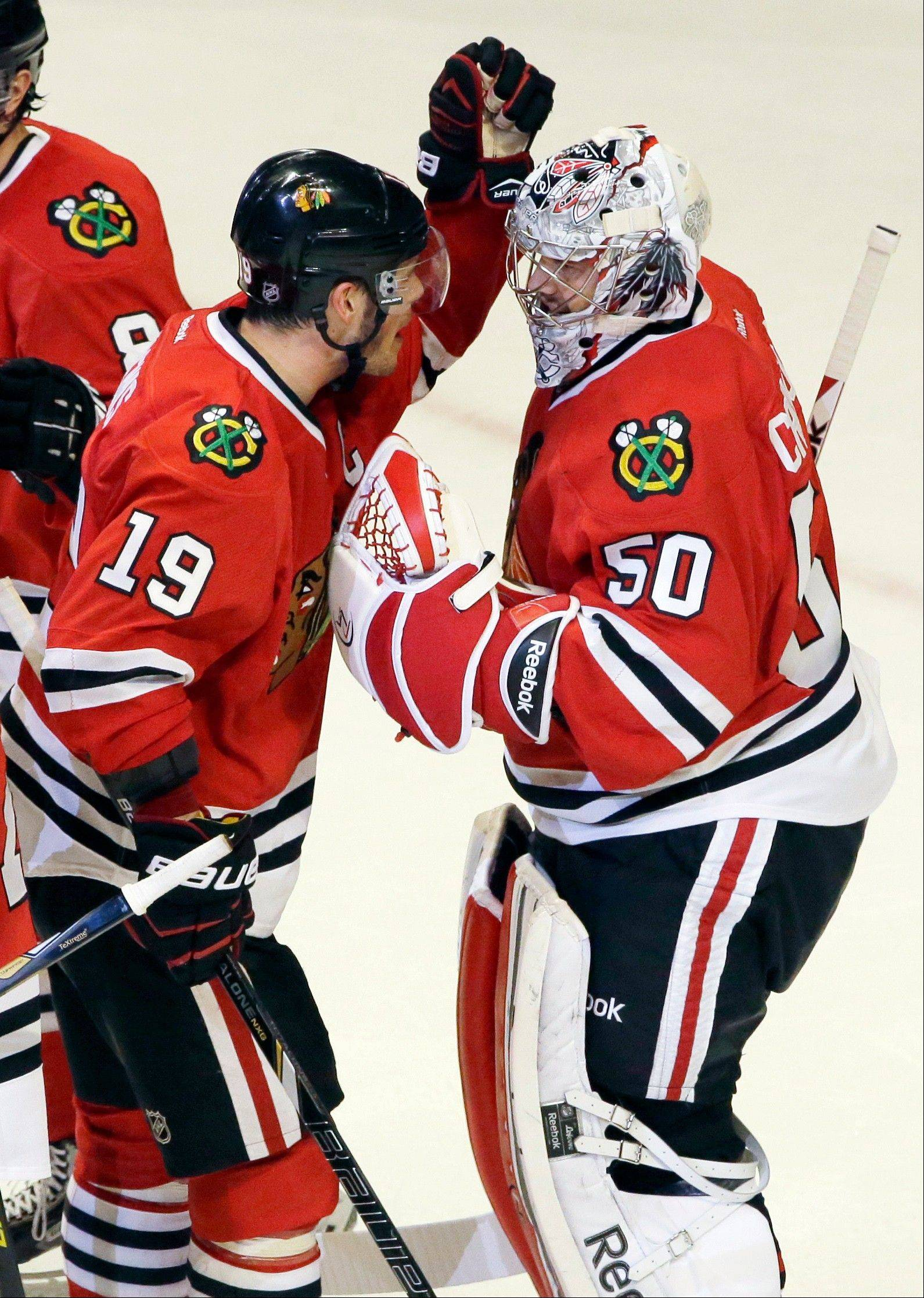 Chicago Blackhawks goalie Corey Crawford, right, celebrates with Jonathan Toews.