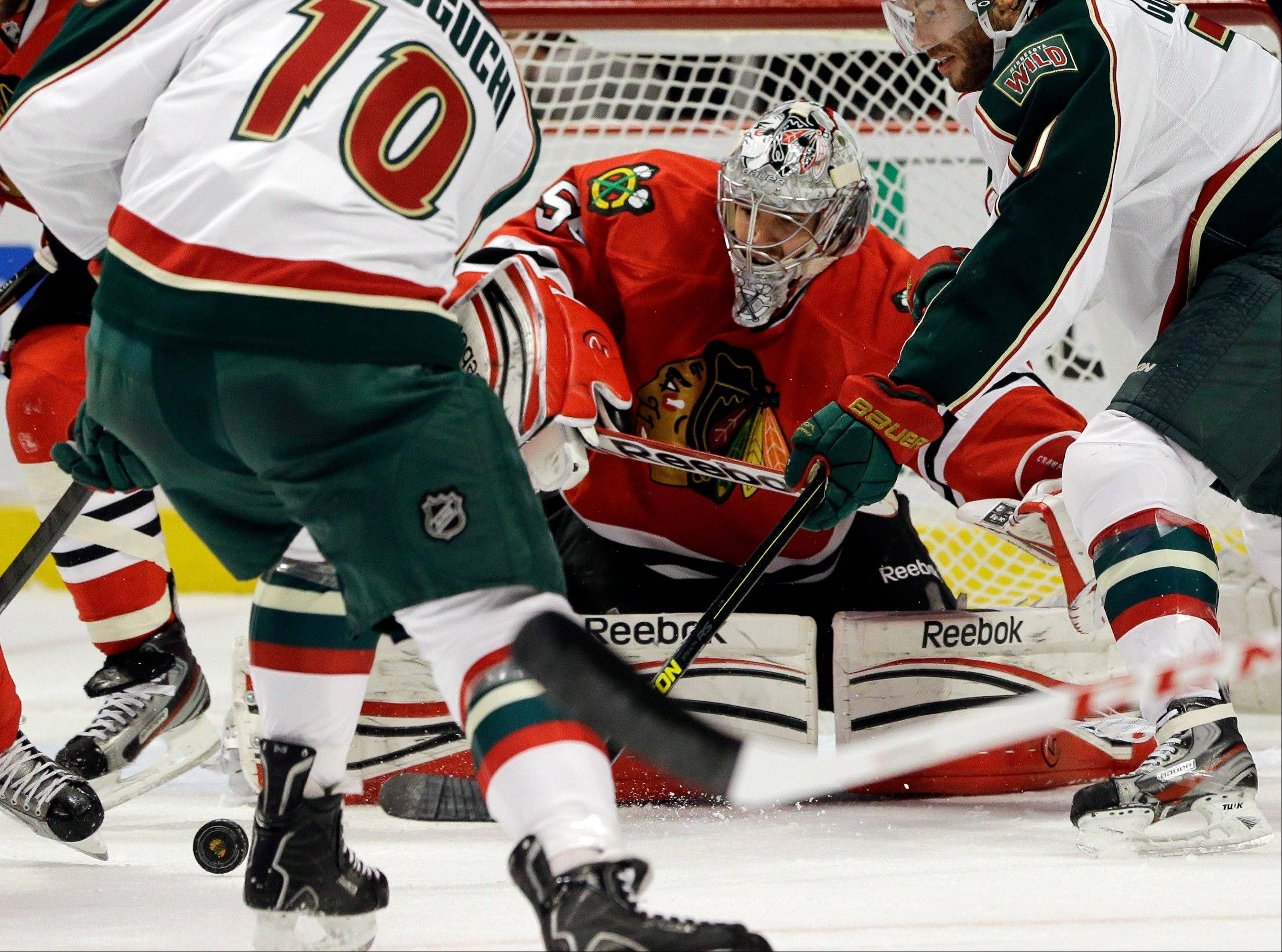 Chicago Blackhawks goalie Corey Crawford (50) blocks a shot by Minnesota Wild's Devin Setoguchi (10) as Matt Cullen (7), right, looks on during the first period of Game 5 of an NHL hockey Stanley Cup first-round playoff series in Chicago, Thursday, May 9, 2013.