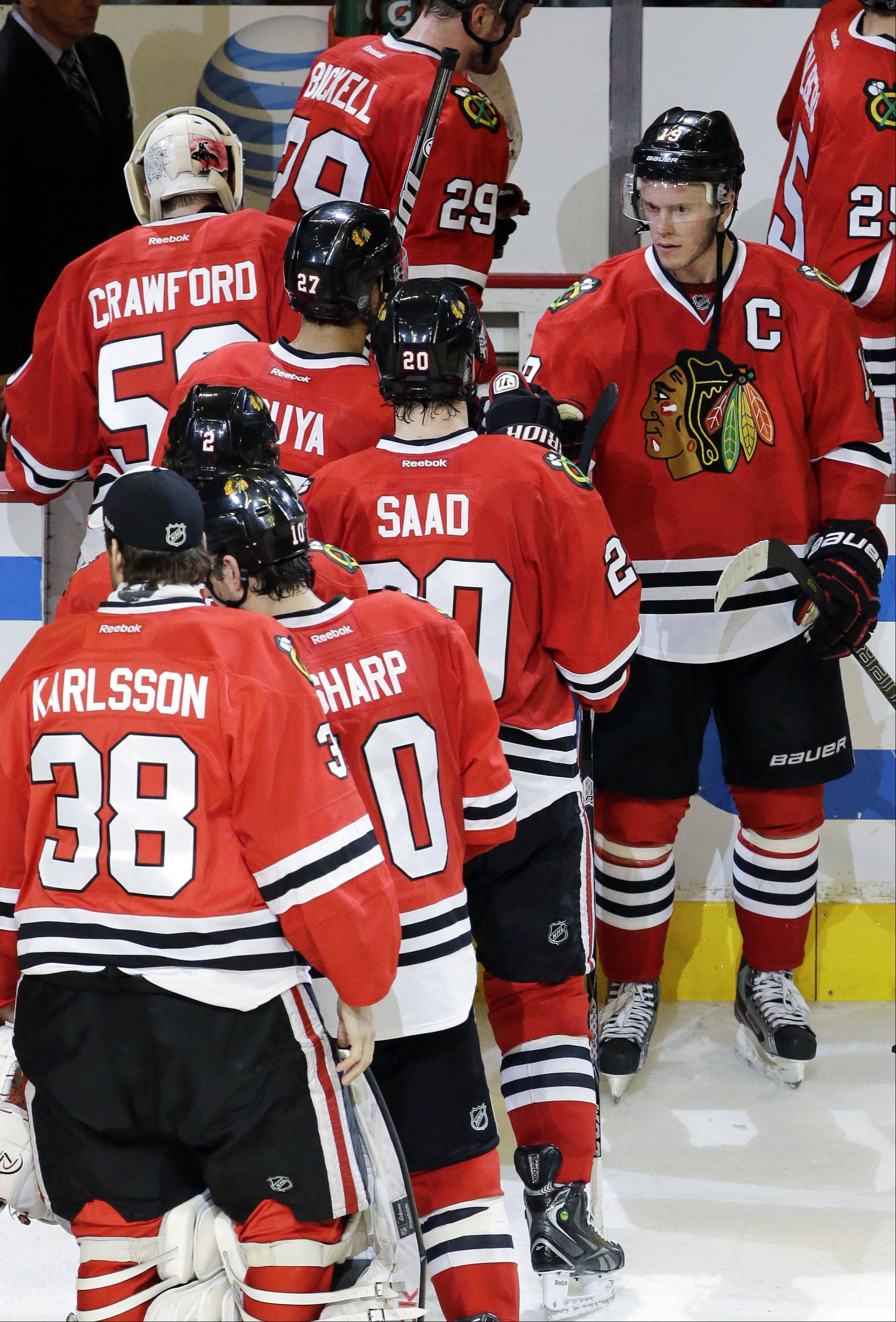 Chicago Blackhawks' Jonathan Toews (19), right, celebrates with teammates after the Blackhawks defeated the Minnesota Wild 5-1 in Game 5 of an NHL hockey Stanley Cup first-round playoff series in Chicago, Thursday, May 9, 2013.