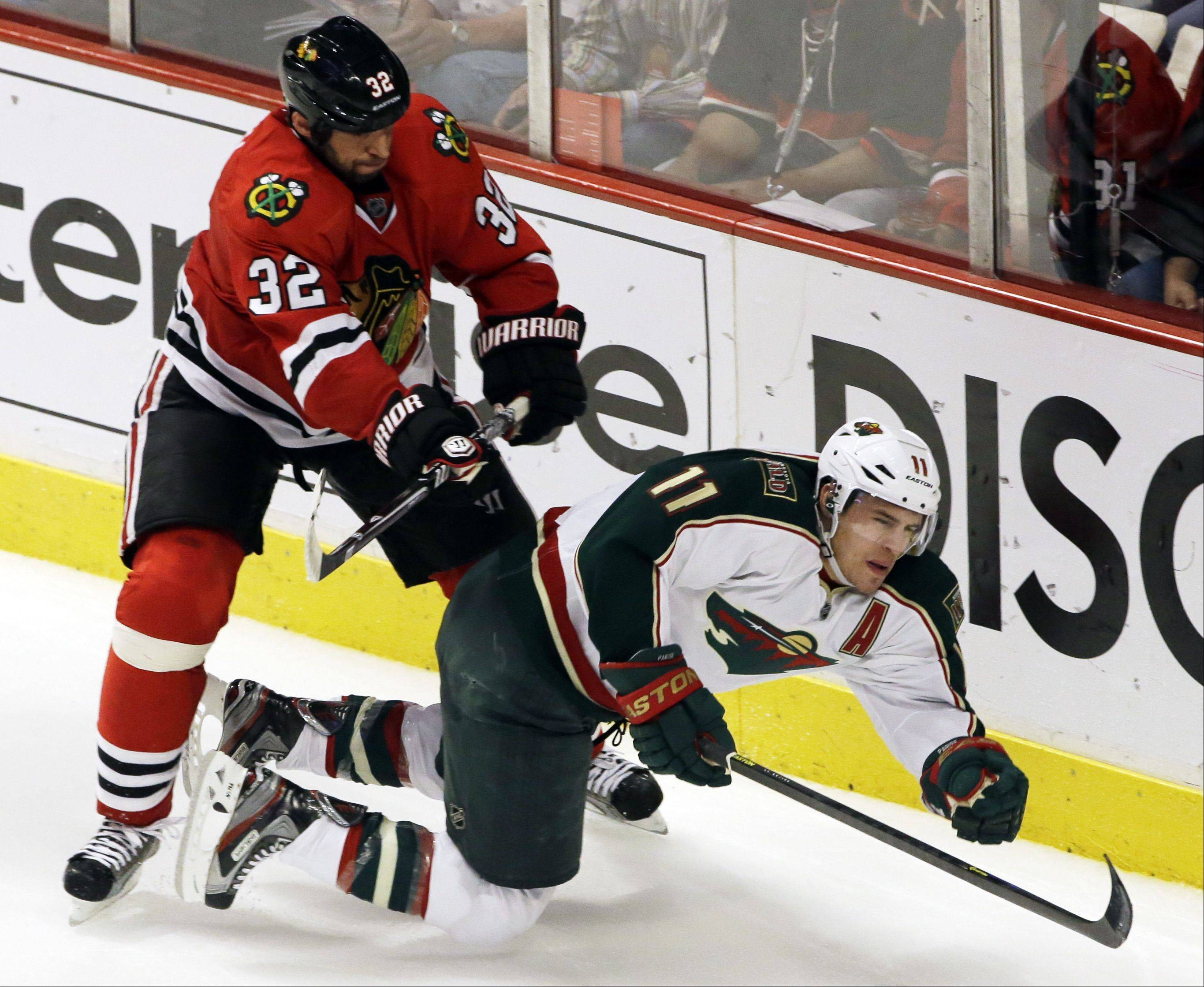 Minnesota Wild's Zach Parise (11) is checked by Chicago Blackhawks' Michal Rozsival (32) during the third period of Game 5 of an NHL hockey Stanley Cup first-round playoff series in Chicago, Thursday, May 9, 2013. The Blackhawks won 5-1.