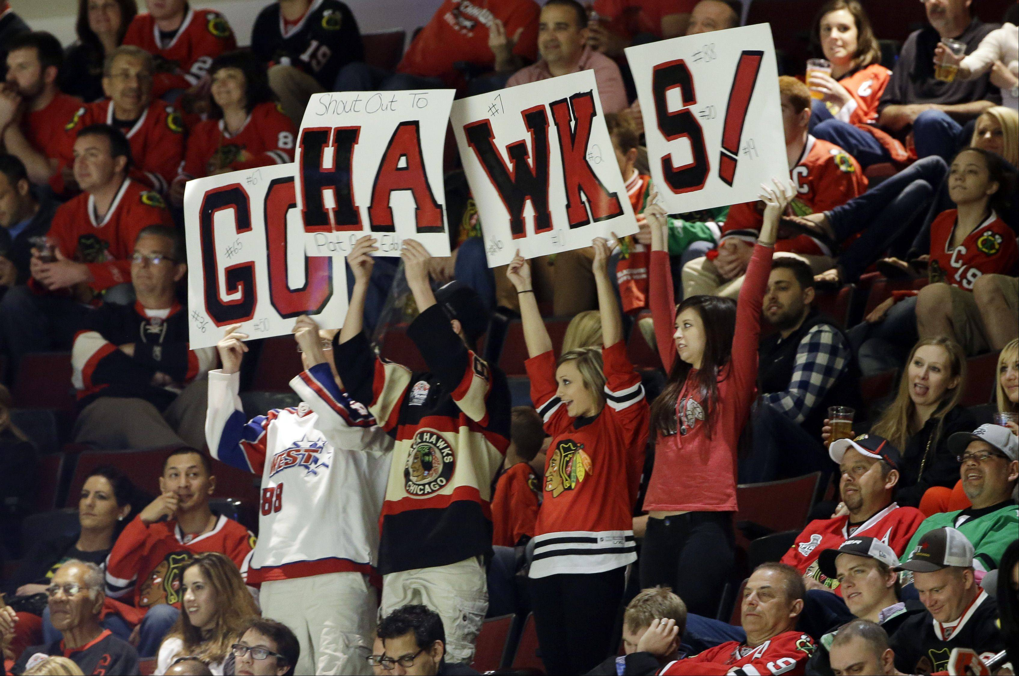 Chicago Blackhawks fans hold signs during the third period of Game 5 of an NHL hockey Stanley Cup first-round playoff series between the Minnesota Wild and the Chicago Blackhawks in Chicago, Thursday, May 9, 2013. The Blackhawks won 5-1.