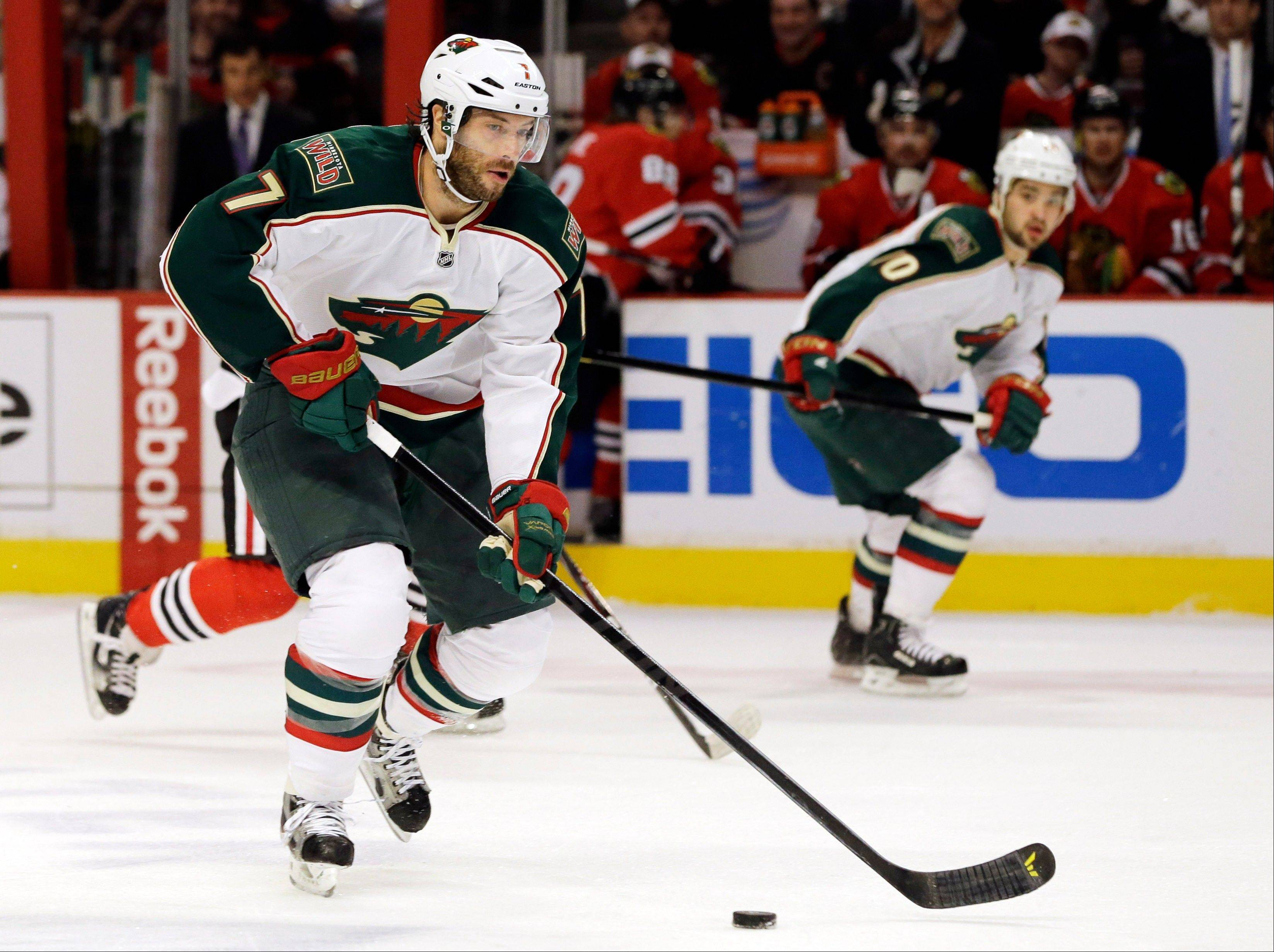Minnesota Wild's Matt Cullen (7) controls the puck as he looks to pass during the first period of Game 5 of an NHL hockey Stanley Cup first-round playoff series against the Chicago Blackhawks in Chicago, Thursday, May 9, 2013.