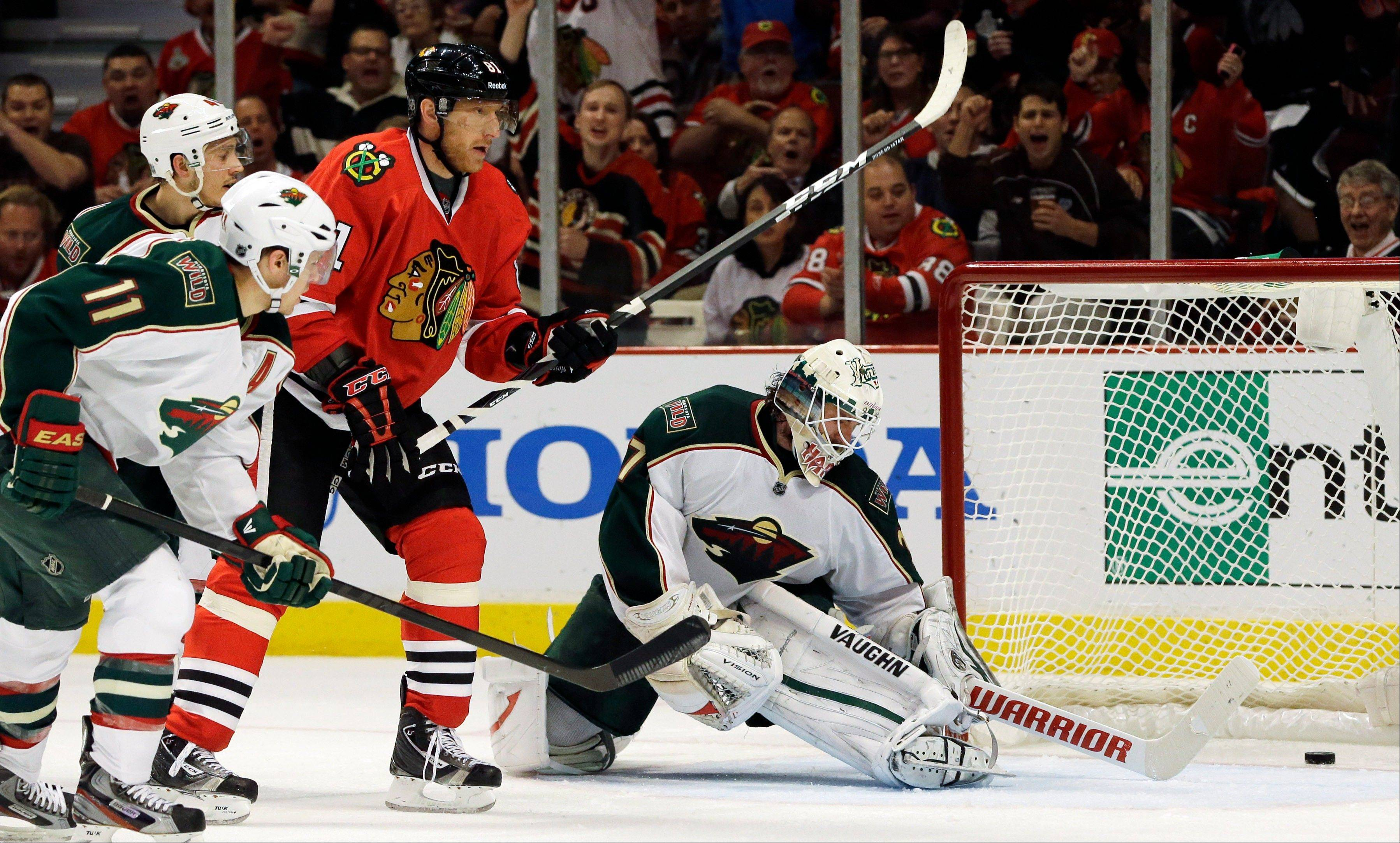 Minnesota Wild goalie Josh Harding, right, cannot save a goal by Chicago Blackhawks' Marian Hossa (81) as Wild's Zach Parise (11) and Jared Spurgeon (46) look on during the second period of Game 5 of an NHL hockey Stanley Cup first-round playoff series in Chicago, Thursday, May 9, 2013.