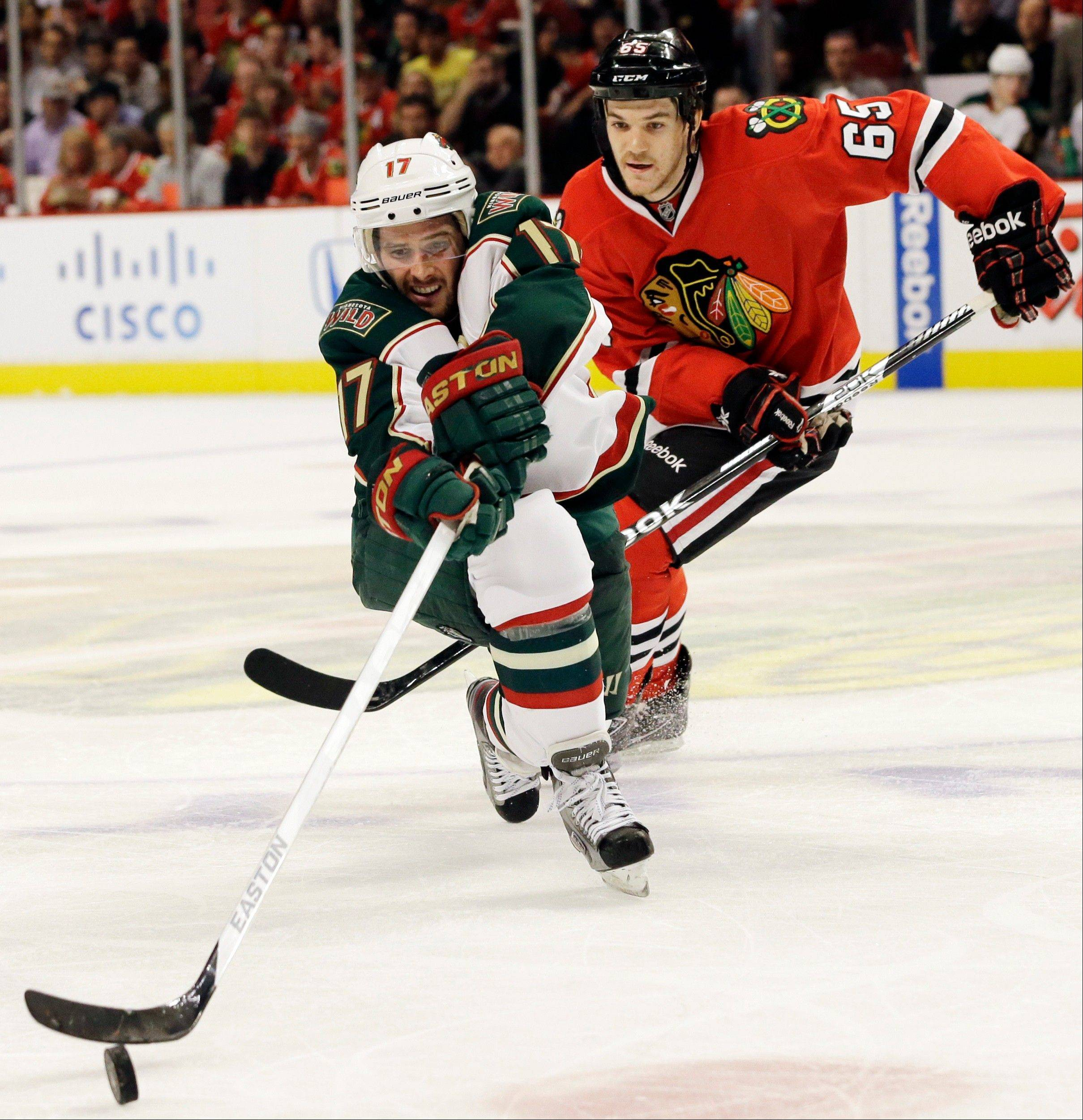 Minnesota Wild's Torrey Mitchell (17) controls the puck against Chicago Blackhawks' Andrew Shaw (65) during the second period of Game 5 of an NHL hockey Stanley Cup first-round playoff series in Chicago, Thursday, May 9, 2013.