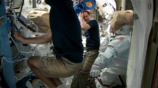 In this image made from video provided by NASA, astronauts Chris Cassidy, foreground, and Tom Marshburn prepare for a possible spacewalk from the International Space Station on Friday, May 10, 2013. NASA will decide later Friday if the two astronauts will step outside the station to work on a leaking coolant line. The line chills power systems but power was rerouted and is operating normally. The six-member crew is not in danger.