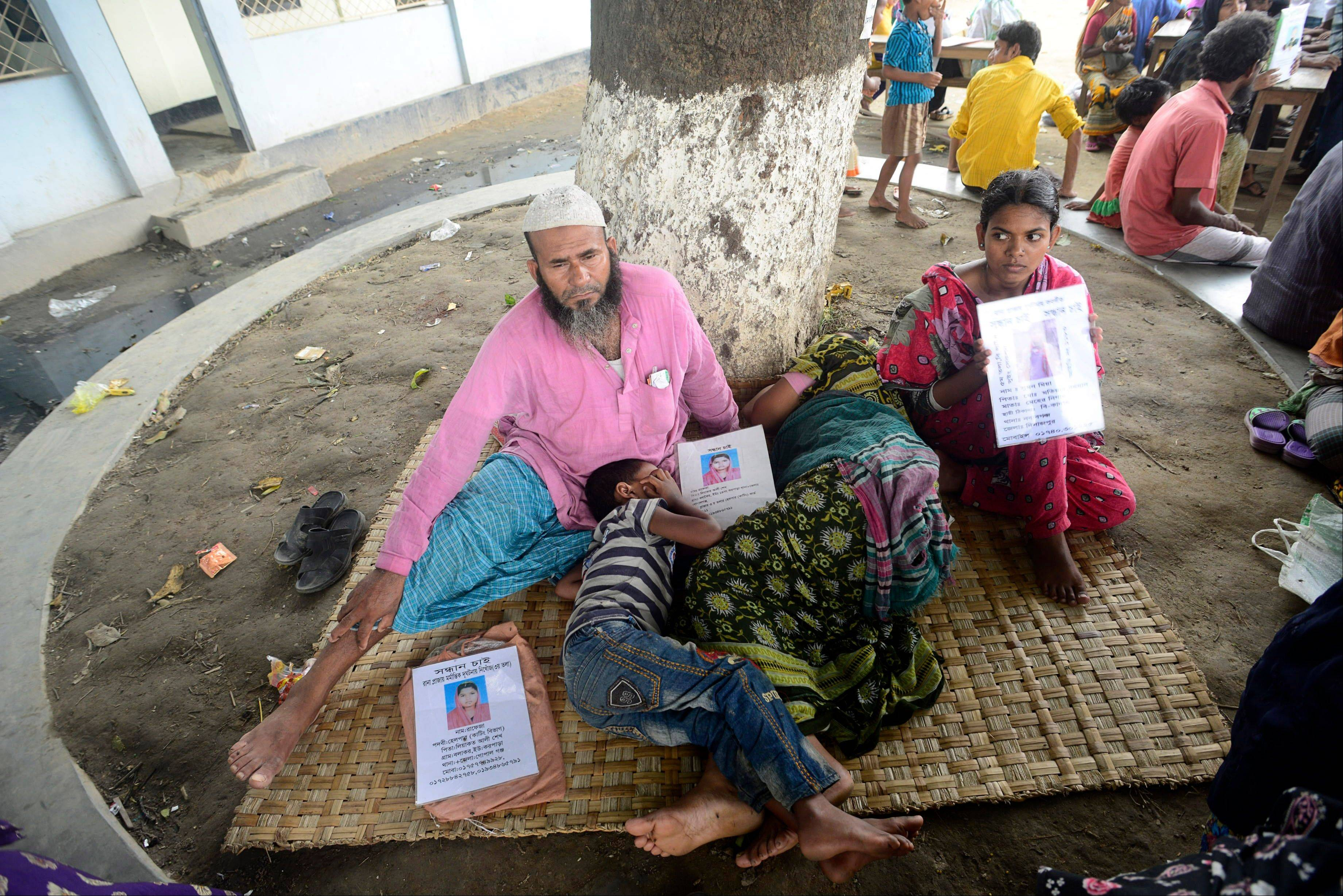 A Bangladeshi man sits Saturday near his sleeping wife and son, with portraits of his missing daughter displayed at a makeshift morgue in Savar, near Dhaka, Bangladesh.