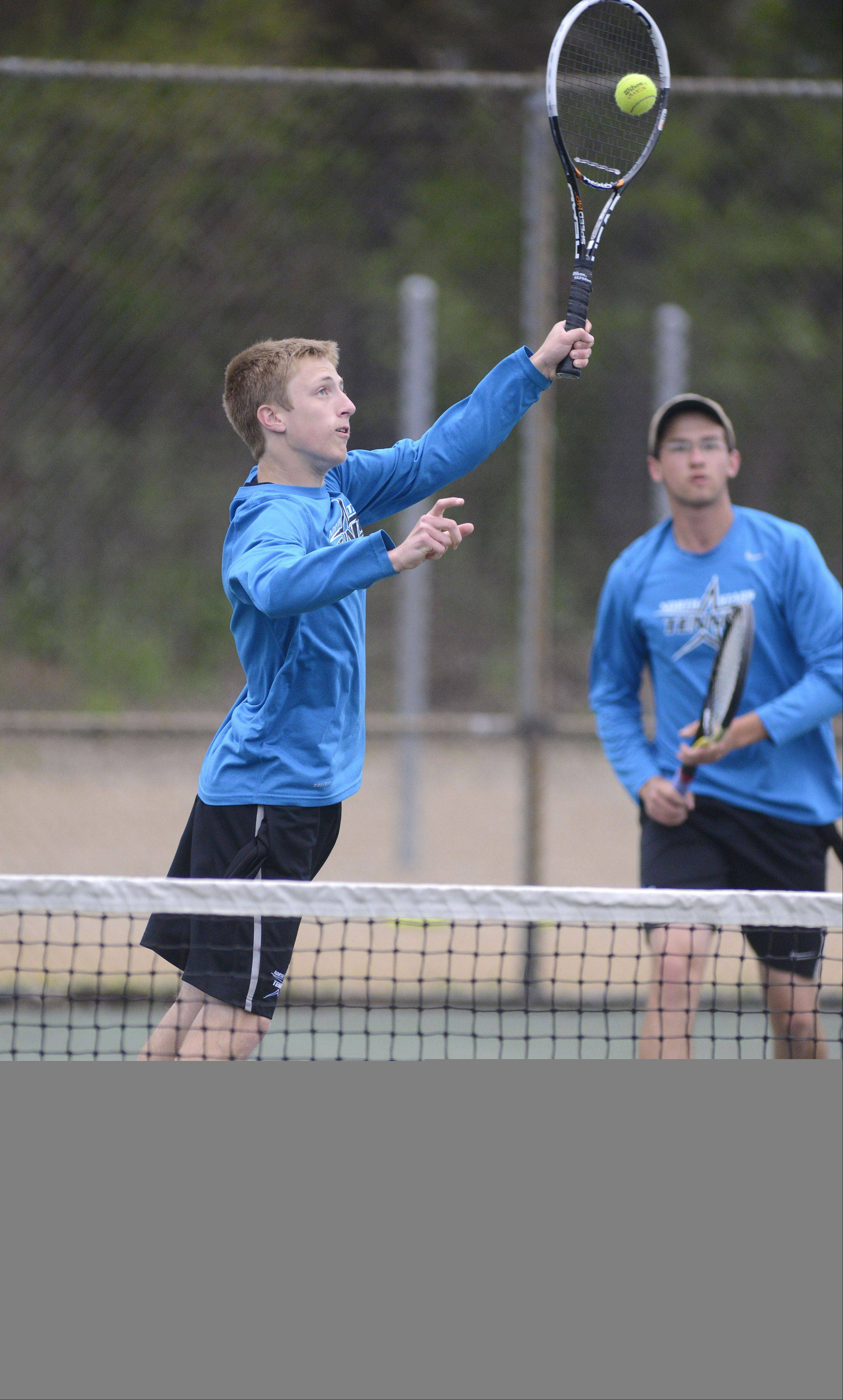 St. Charles North's Keith Hedges returns a hit from Batavia in the first place, first doubles match with teammate Grant Spellman in the Upstate Eight Conference at Elgin High School on Saturday, May 11.