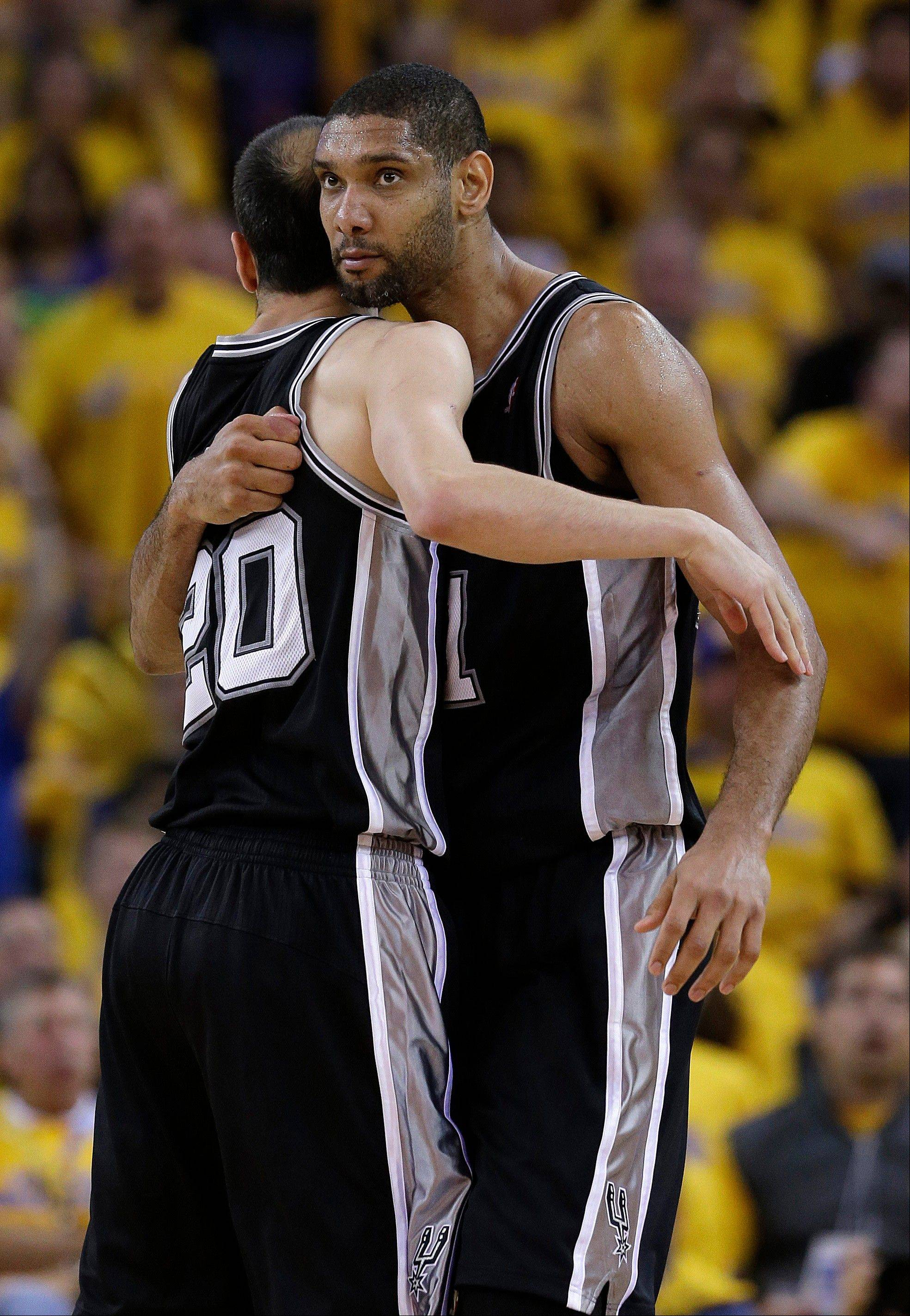 San Antonio Spurs forward Tim Duncan, right, hugs shooting guard Manu Ginobili (20), after Duncan made a basket during the fourth quarter of Game 3 of a Western Conference semifinal NBA basketball playoff series in Oakland, Calif., Friday, May 10, 2013. The Spurs won 102-92. (AP Photo/Jeff Chiu)