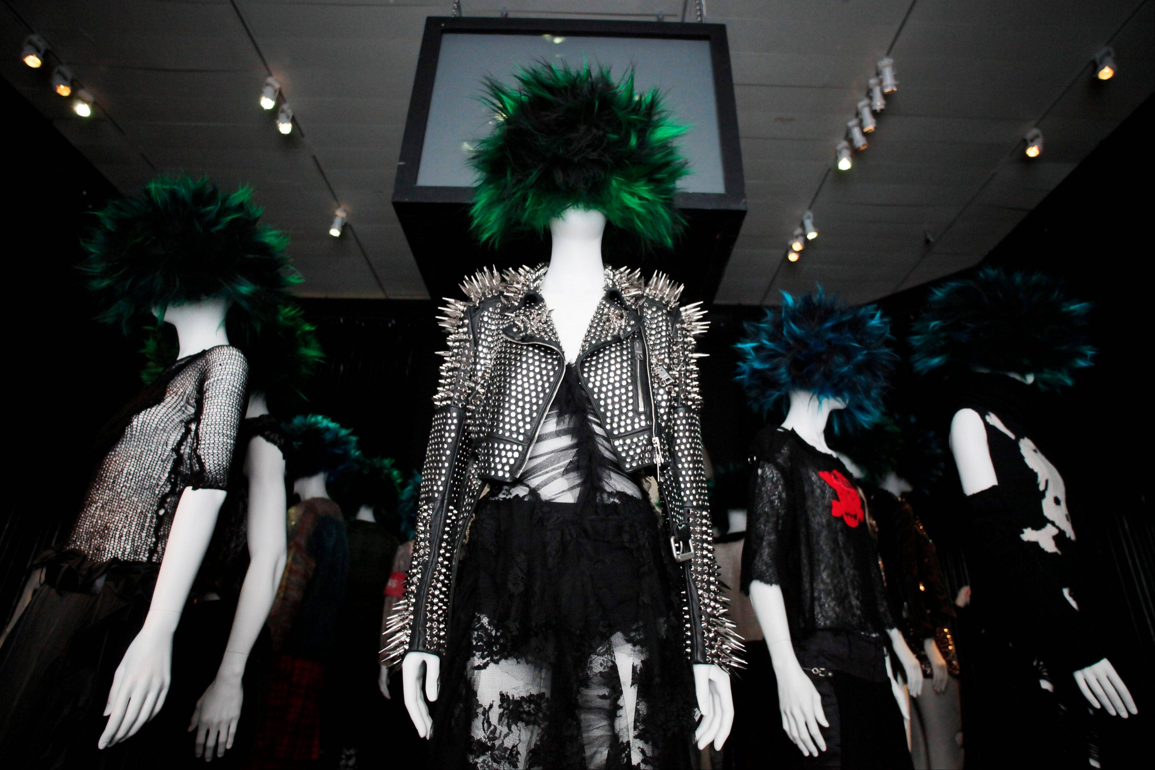 "A design, center, by Christopher Bailey for Burberry is shown at the Metropolitan Museum of Art's exhibit, ""Punk: Chaos to Couture,"" in New York. The show, which examines punk's impact on high fashion from the movement's birth in the 1970s through its continuing influence today."