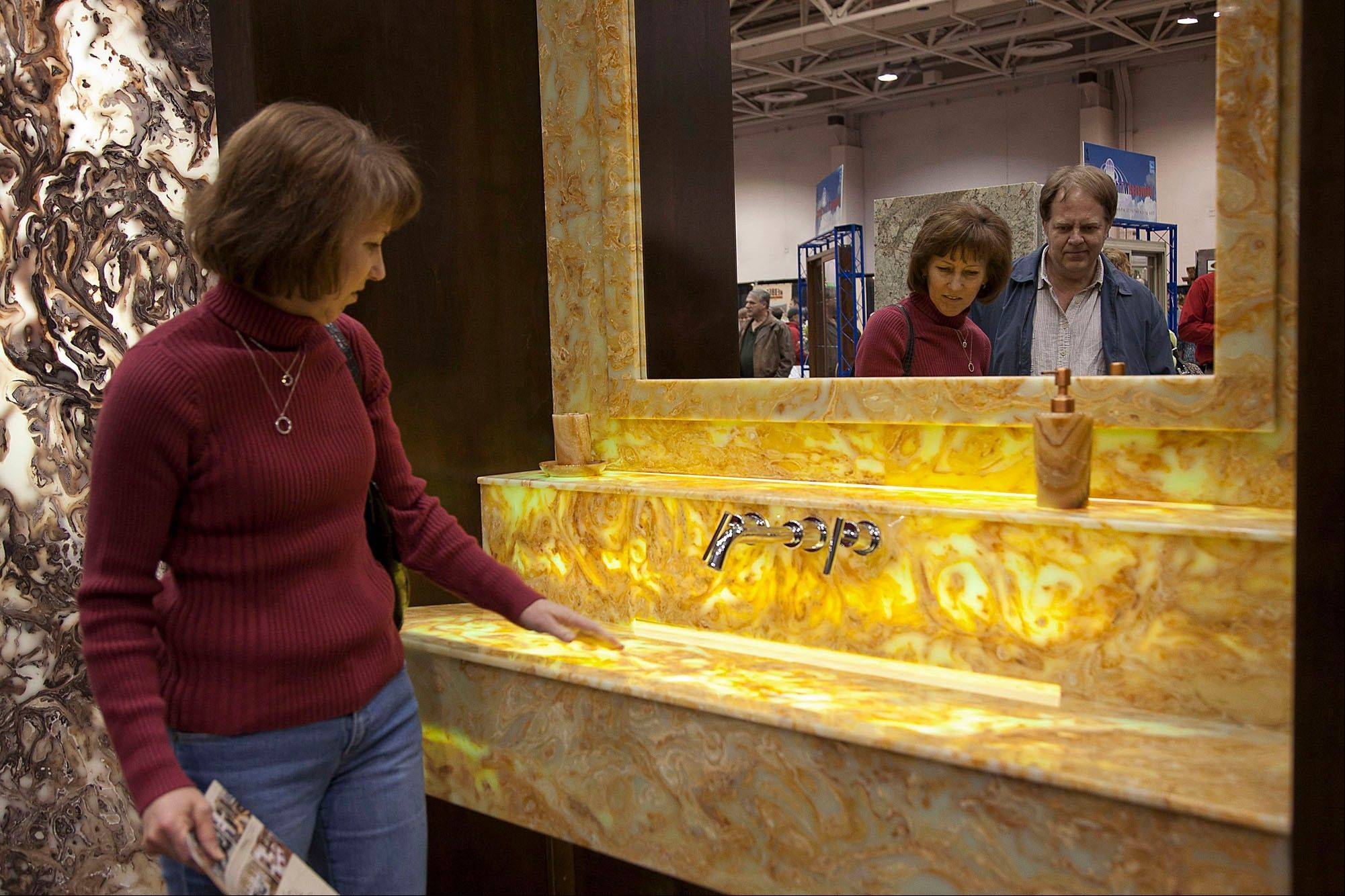 Elaine Dorsher looks at an artificial stone sink at the Universal Stone Inc. display at the Minneapolis Home & Garden Show in Minneapolis.