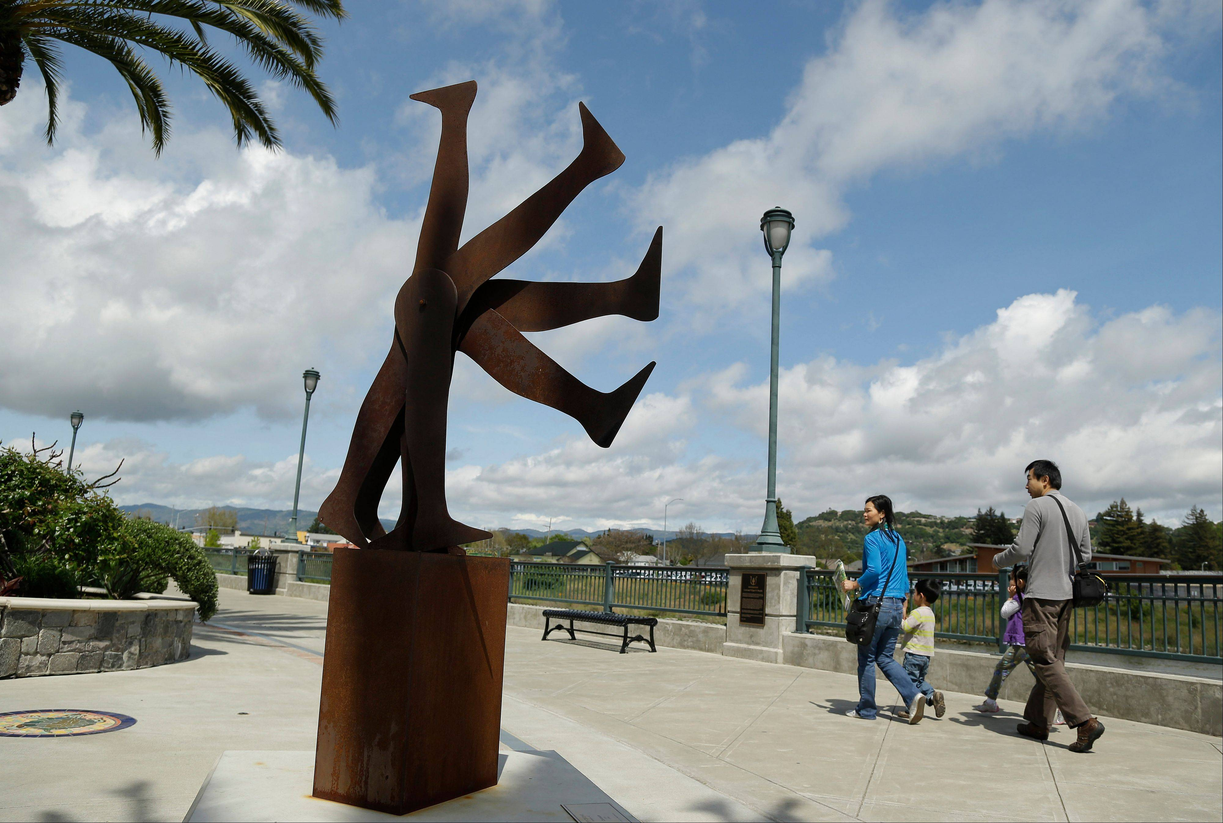 "A family walks along the river past a piece called ""Continuum"" that is part of an art walk in Napa, Calif."