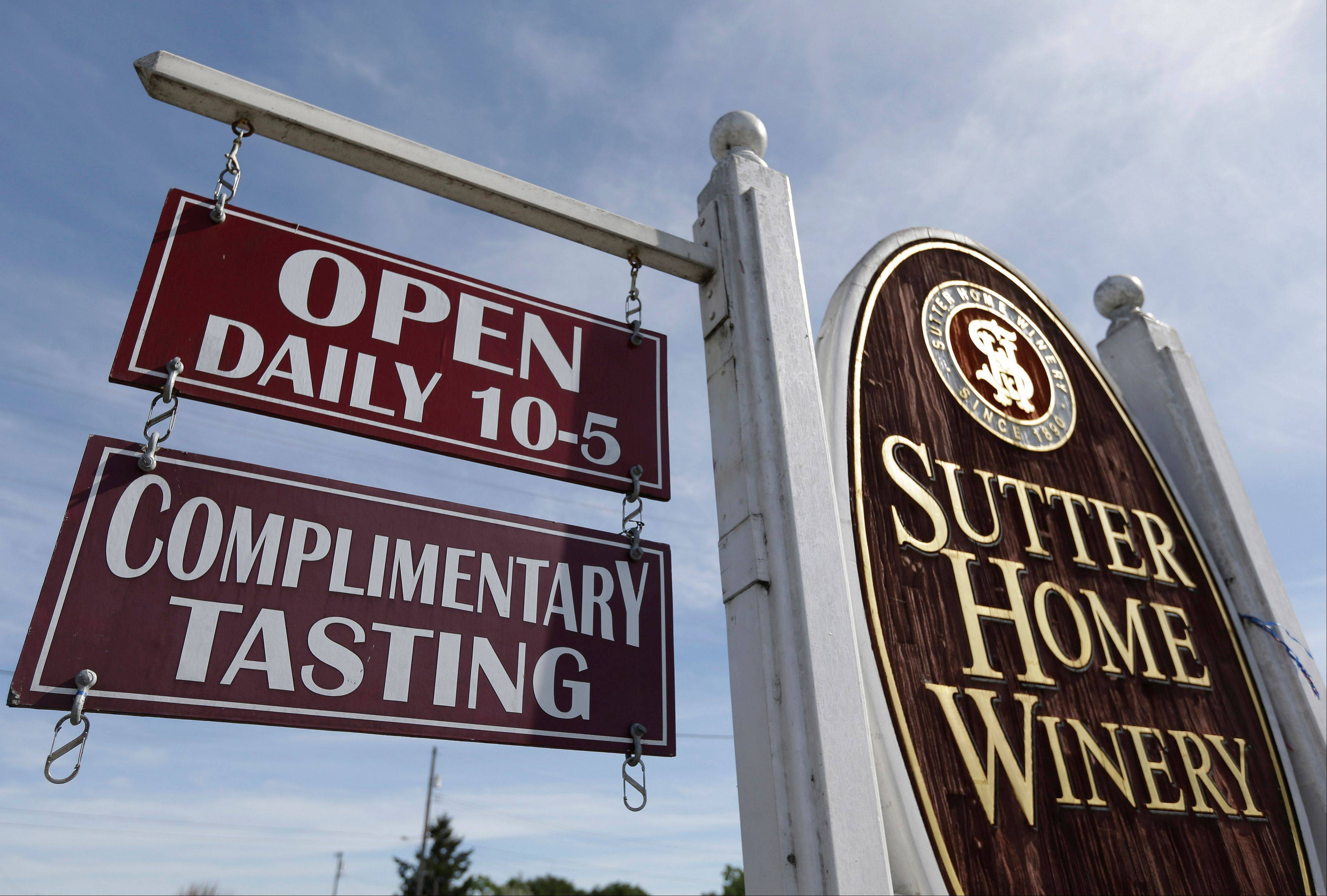 A sign for complimentary tastings hangs outside Sutter Home Winery in St. Helena, Calif.