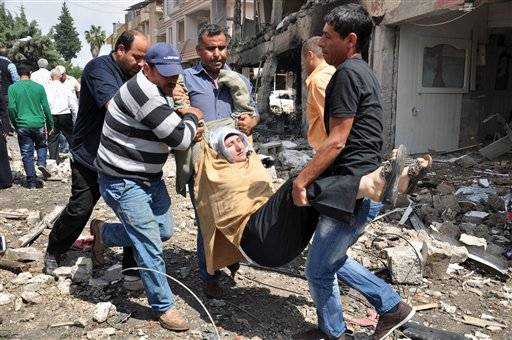 People carry a woman injured in a blast in Reyhanli, near Turkey's border with Syria, Saturday, May 11, 2013. Two car bombs exploded in a Turkish town near the border with Syria on Saturday, killing and injuring scores of people officials and media reports said.