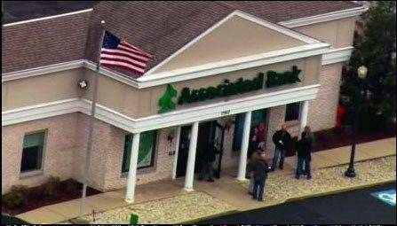A suspect in a bank robbery was shot and killed by police near the Associated Bank in Richmond on Friday, but no one else was injured.