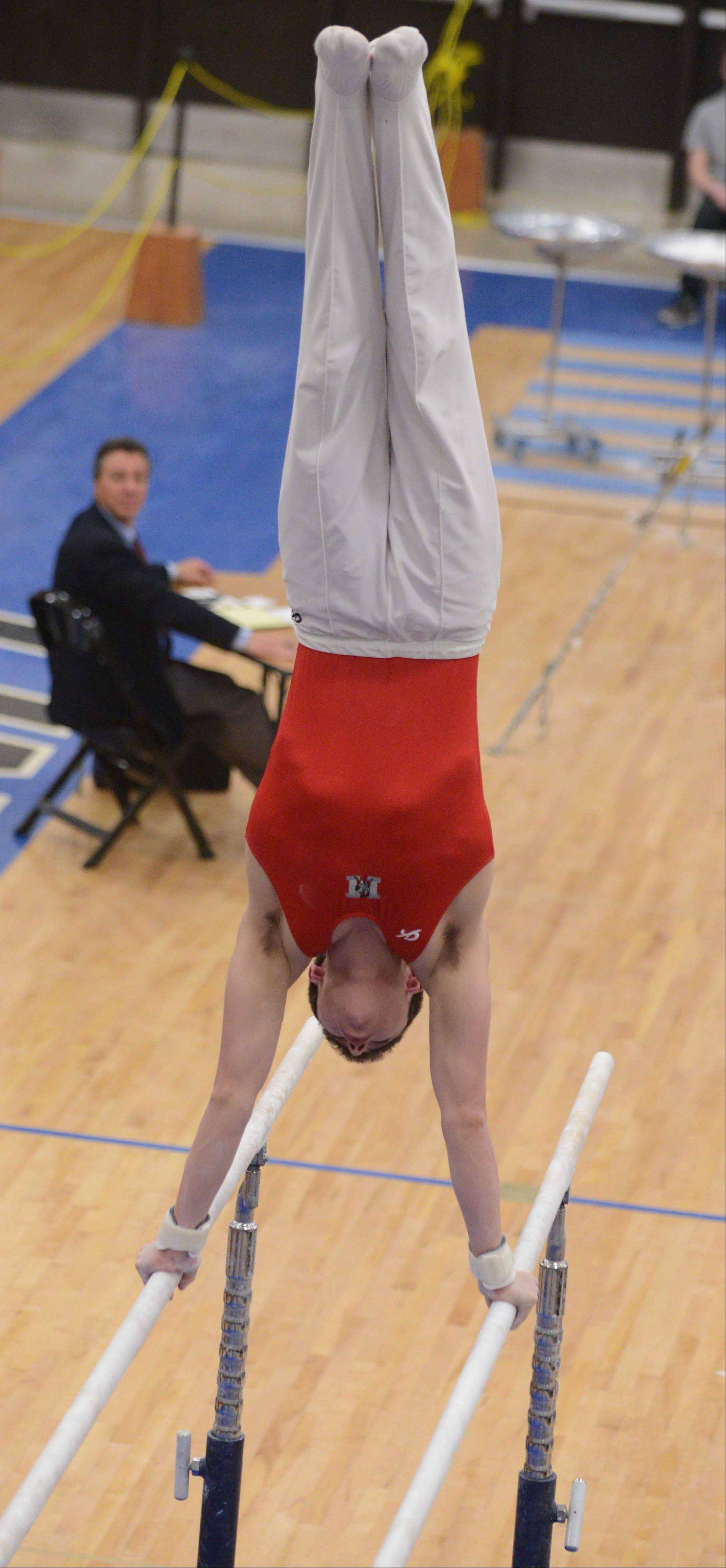 Colin McCarthy of Mundelein performs on parallel bars during the boys gymnastics state finals at Lincoln-Way East on Saturday.