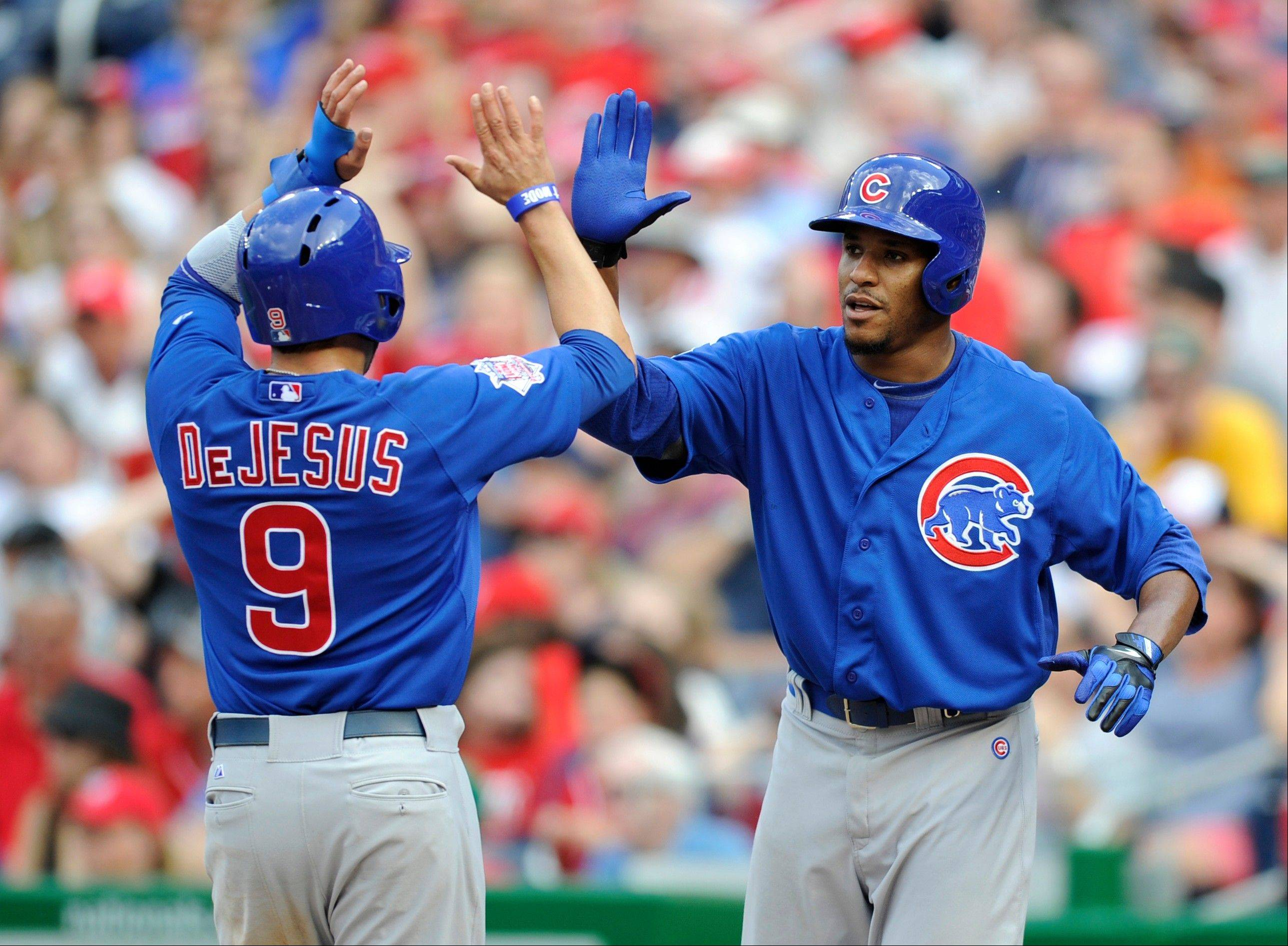 Cubs starting pitcher Edwin Jackson, right, gives teammate David DeJesus a high-five Saturday after they scored on a single by Anthony Rizzo during the fifth inning against the Washington Nationals in Washington.