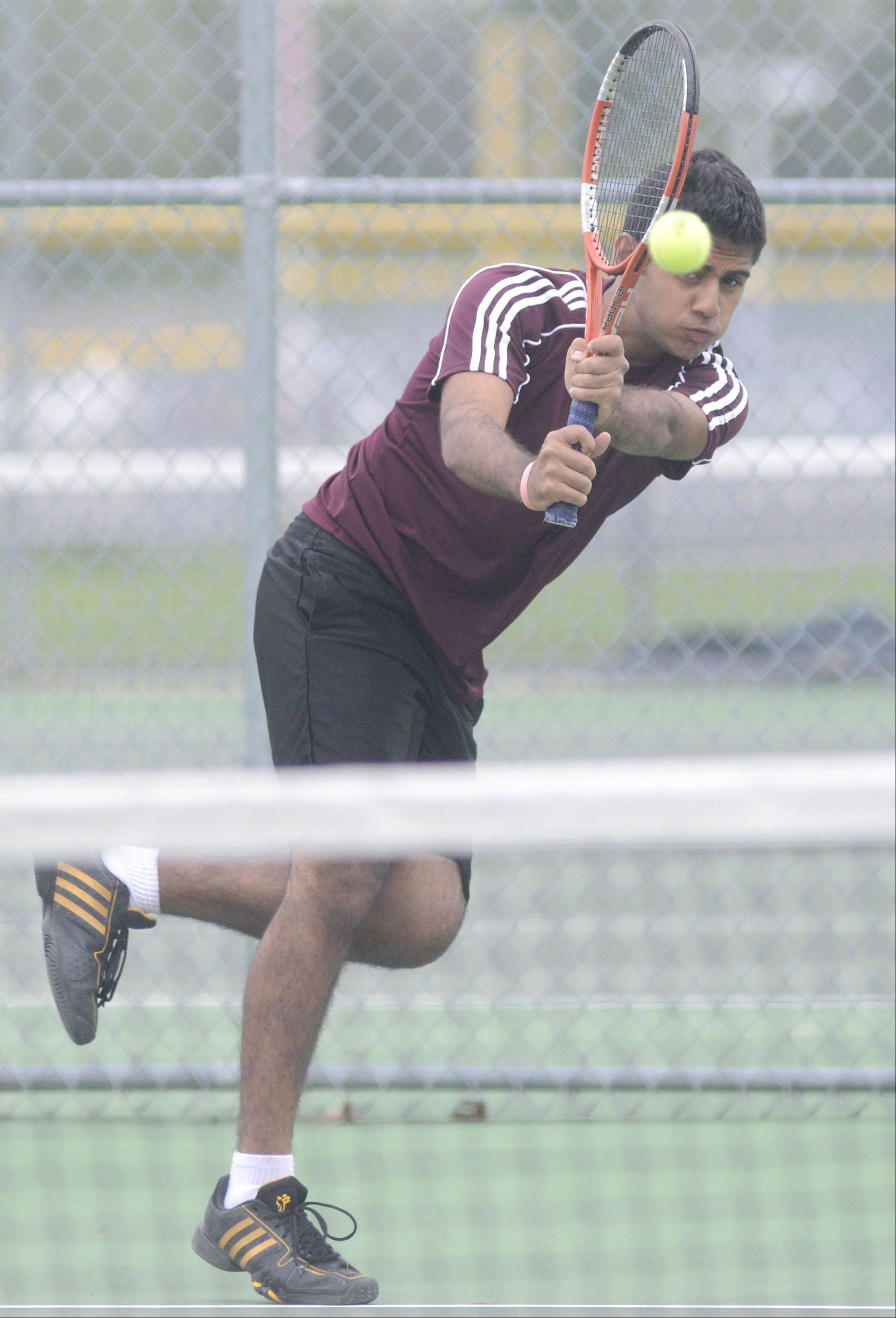 Elgin's Reza Khan returns a serve to St. Charles East's Justin Bowman in the third place match first singles match in the Upstate Eight Conference at Elgin High School on Saturday, May 11.