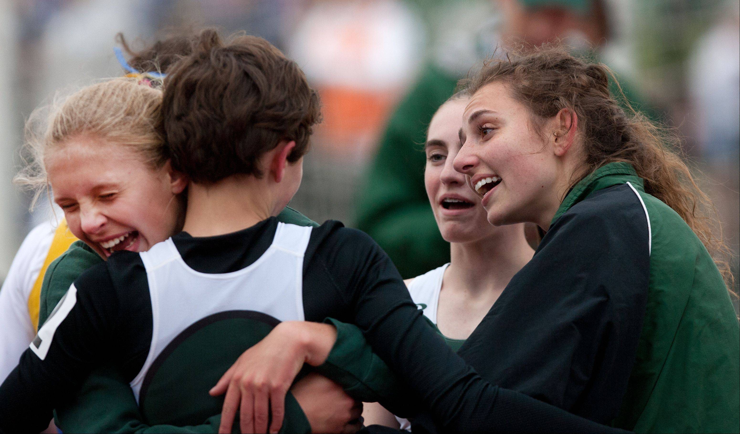 Glenbard West's Christina Sedall, facing away, celebrates her team's 3,200 Meter Relay second play finish during the York Girls Track and Field Sectional meet.