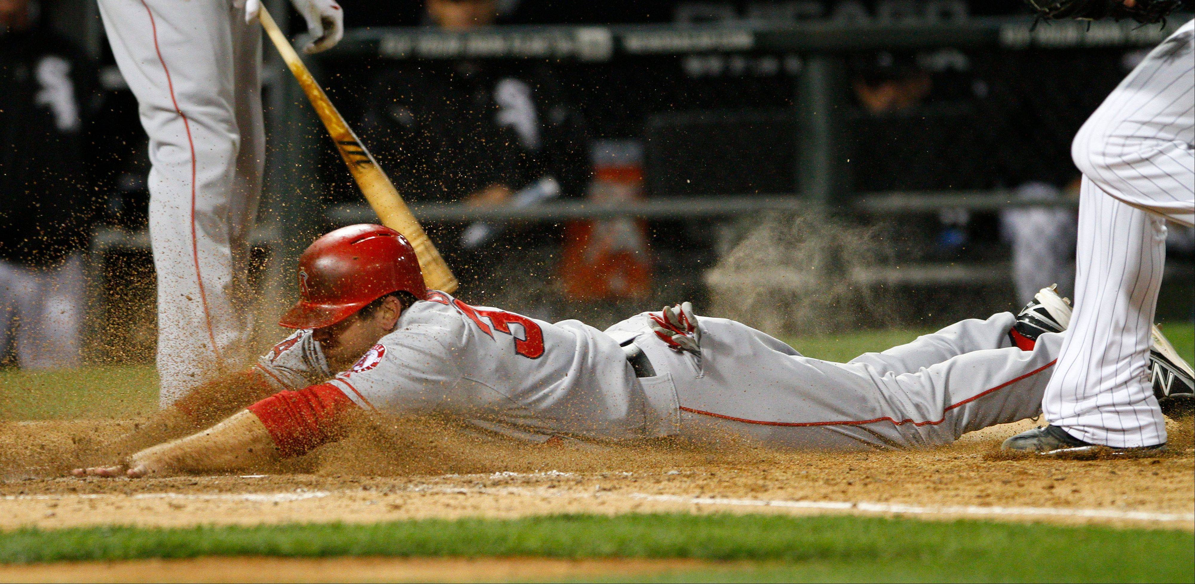 Los Angeles Angels' J.B. Shuck dives across home plate after a passed ball in the seventh inning against the White Sox in a baseball game in Chicago on Friday, May 10, 2013.