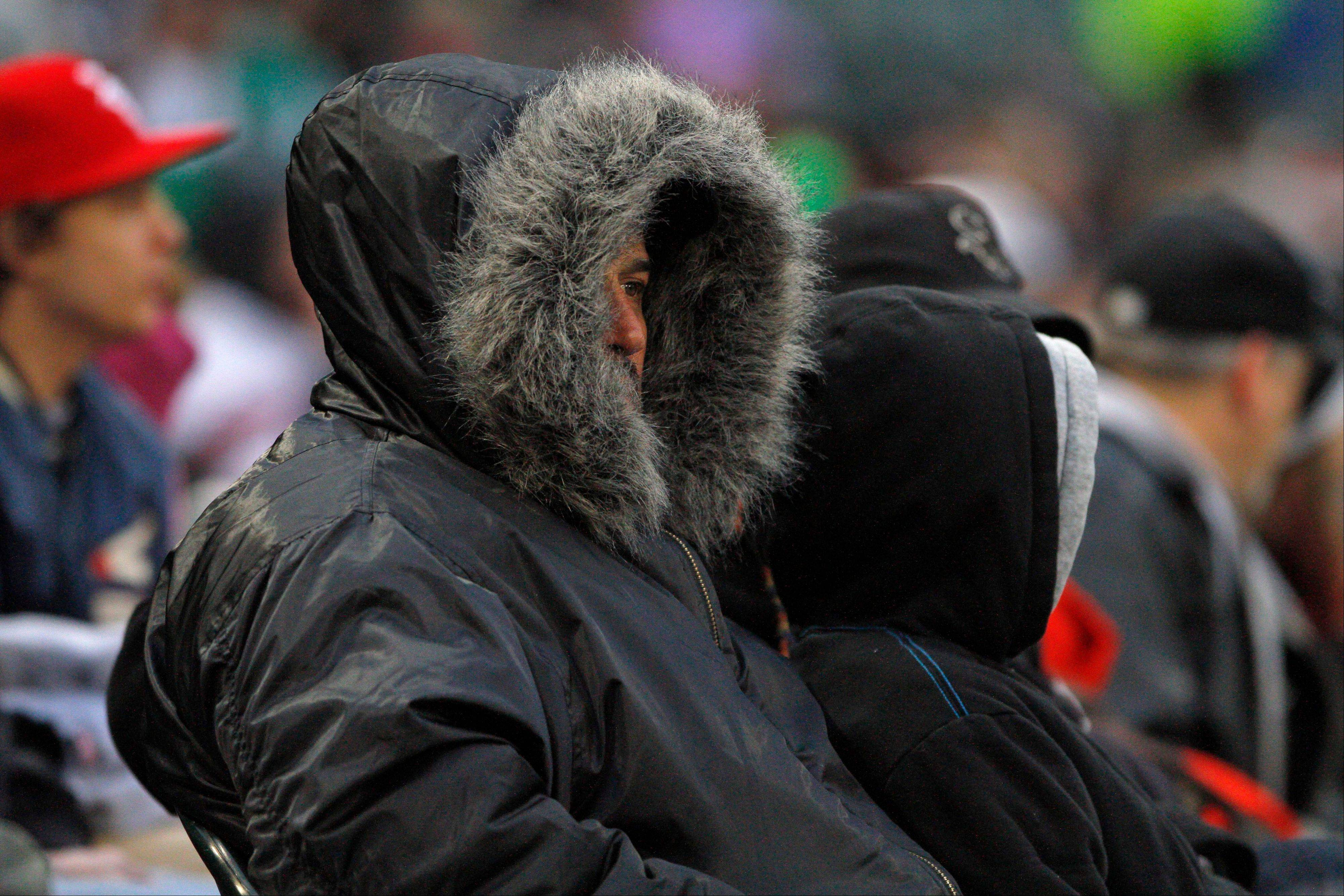 Fans bundle up as the temperature dipped below 40 degrees during a baseball game between the Chicago White Sox and the Los Angeles Angels in Chicago on Friday, May 10, 2013.
