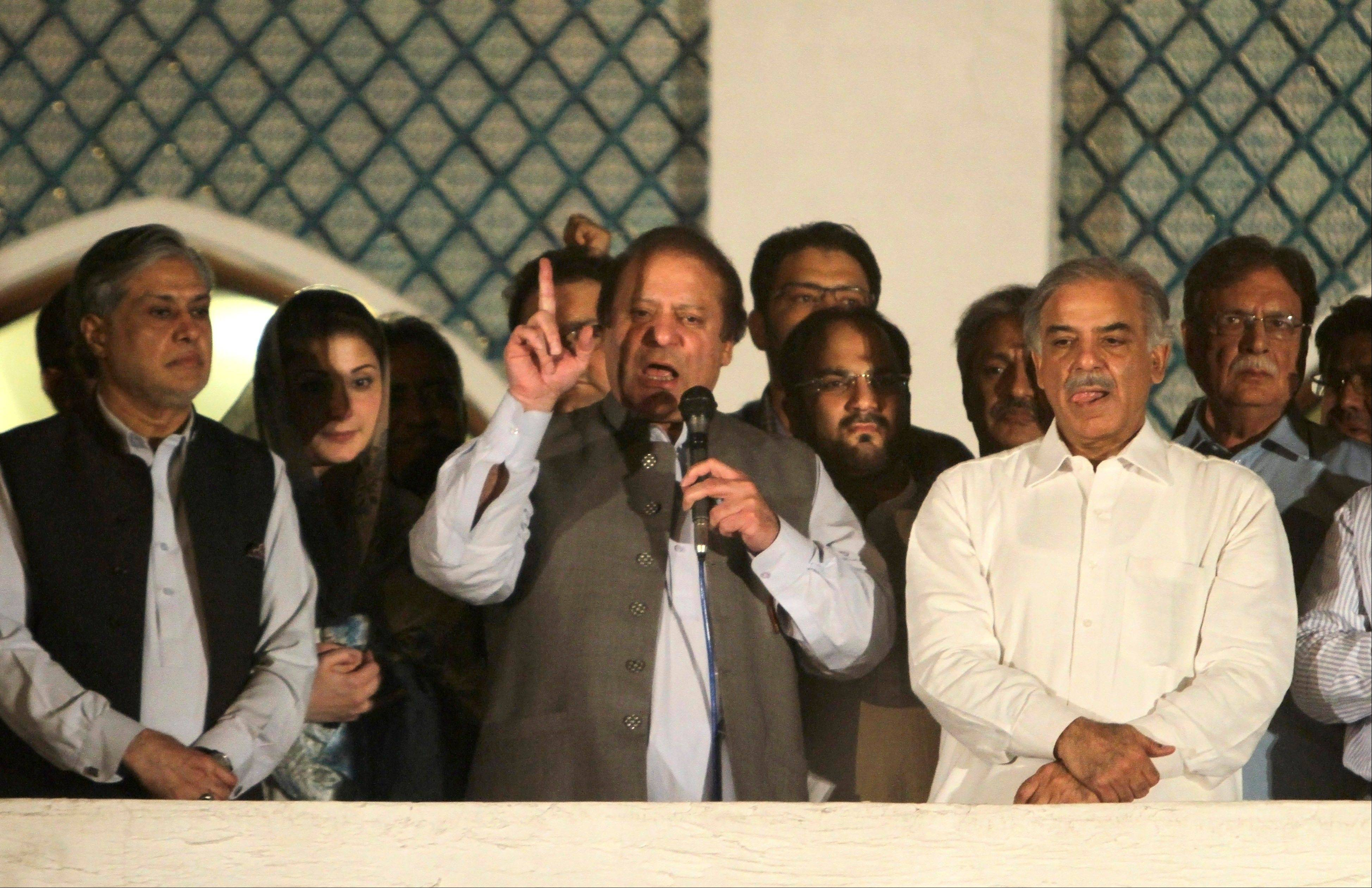 Former Prime Minister and leader of the Pakistan Muslim League-N party Nawaz Sharif, center, was headed for victory Sunday in a landmark election and the chance to run the country for a record third time.