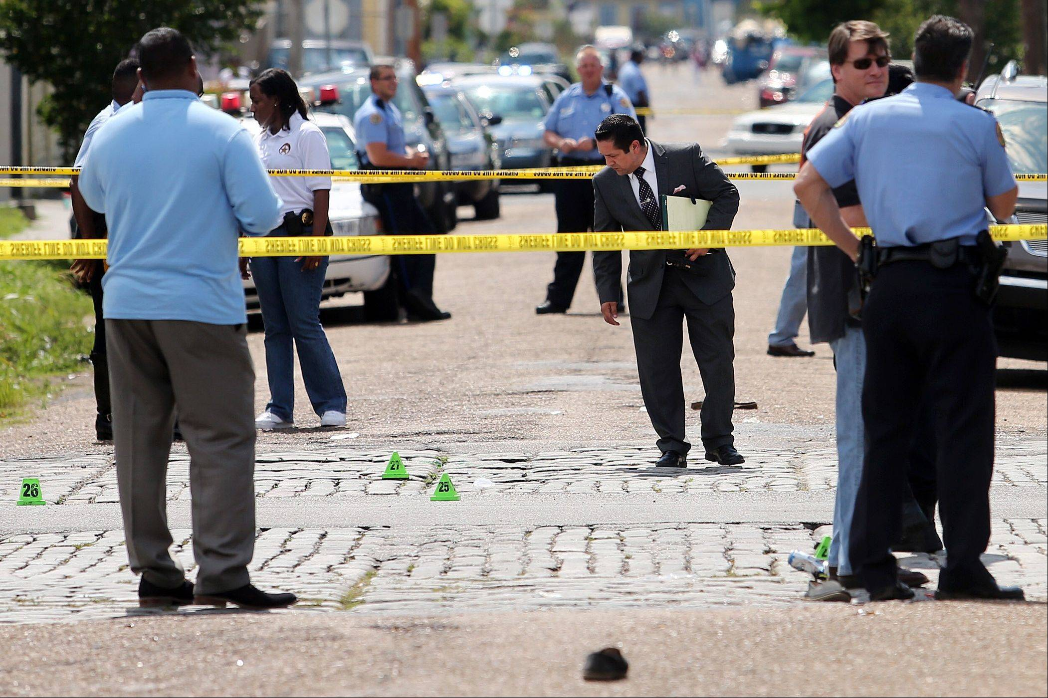 New Orleans police officers investigate the scene of gunfire that broke out during a Mother�s Day parade Sunday.