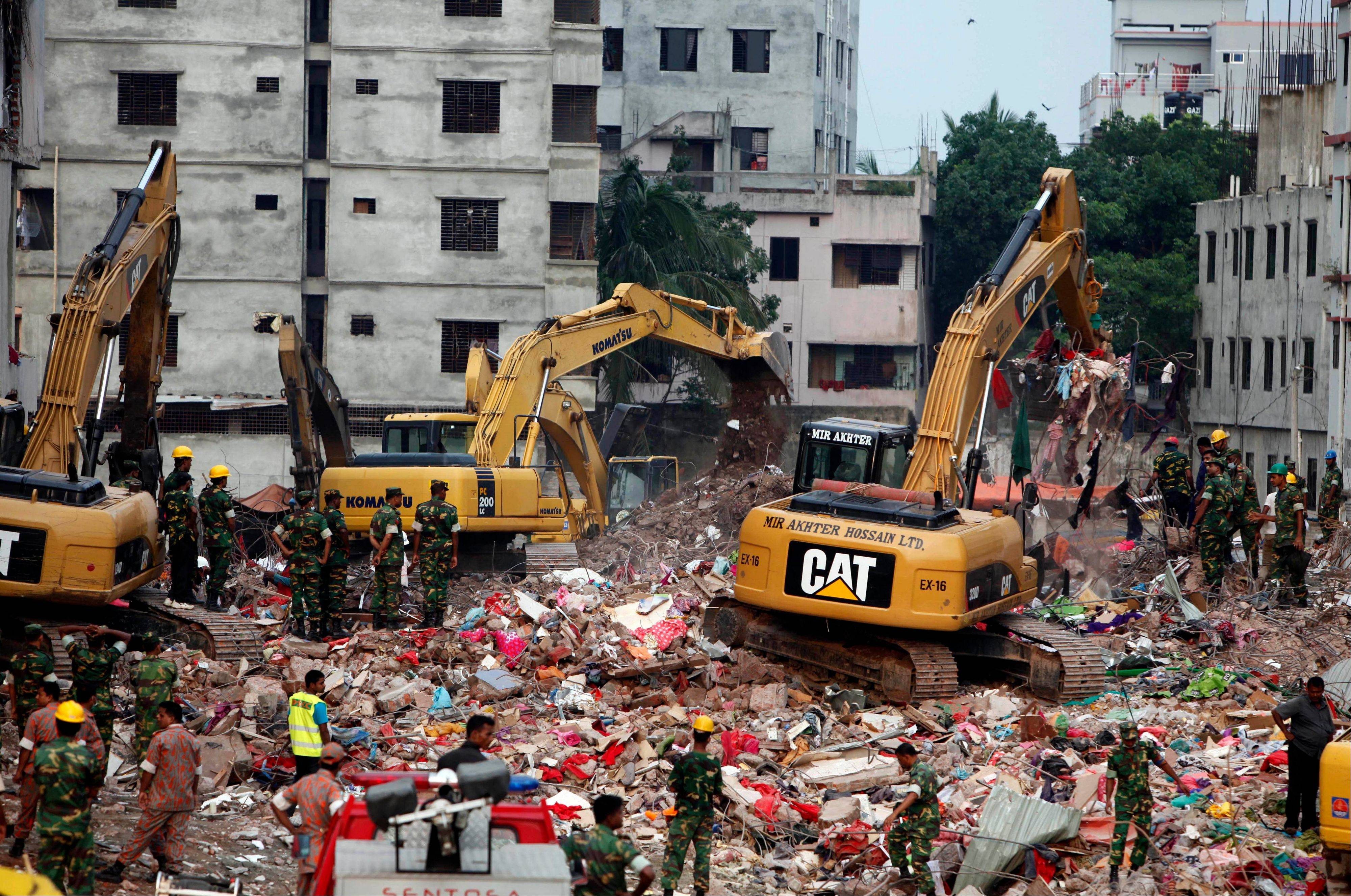 Bangladeshi rescuers use heavy machinery to clear rubble of a garment factory building that collapsed April 24 as they continue searching for bodies in Savar, near Dhaka, Bangladesh, Sunday.