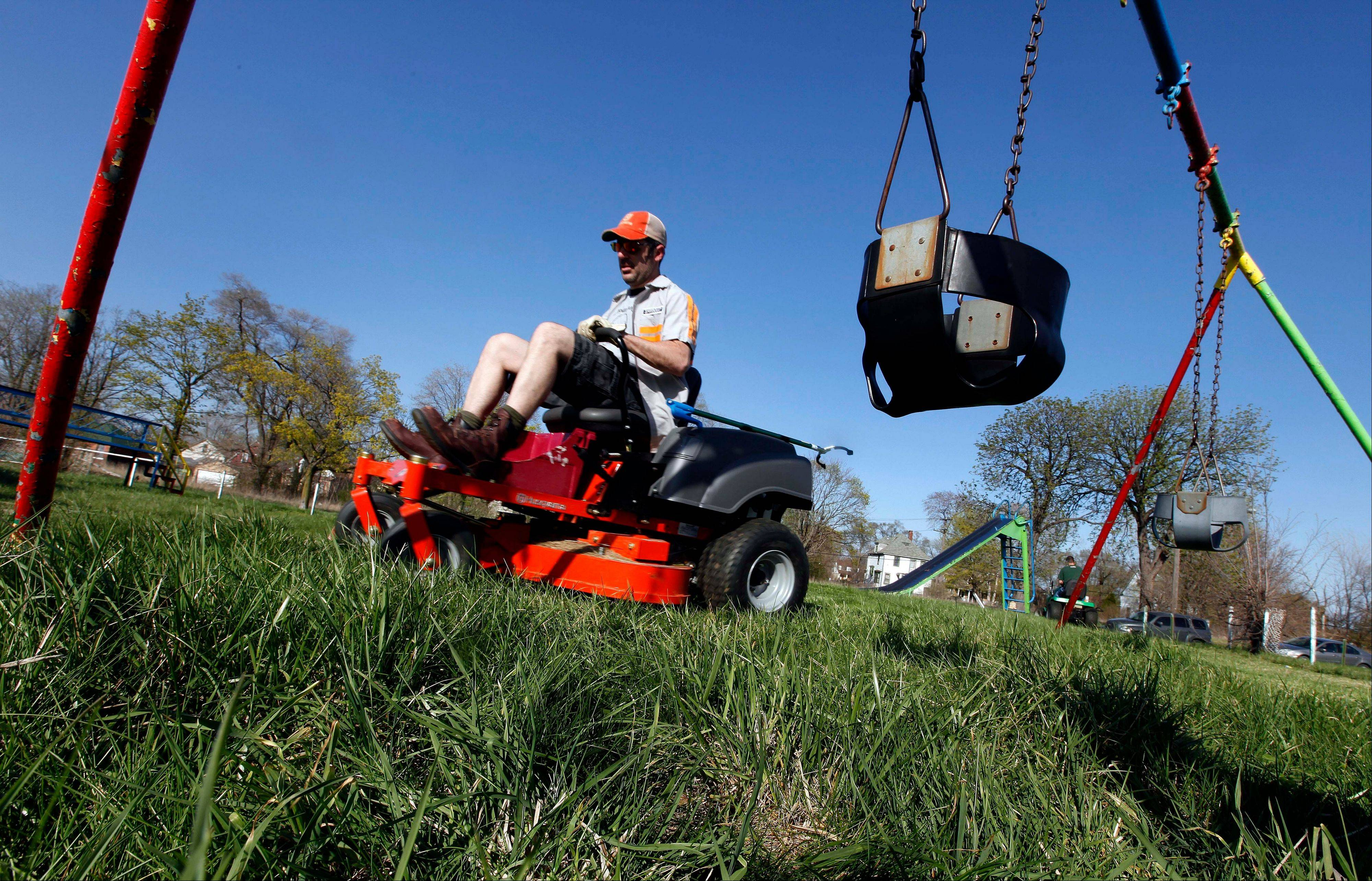Mower gang member Tom Nardone of Birmingham drives a riding mower at Duweke Park in Detroit earlier this month. The Mower Gang, a group of volunteer lawn mower riders, adopt parks beginning in the spring and keep them free of high-grass throughout the summer.