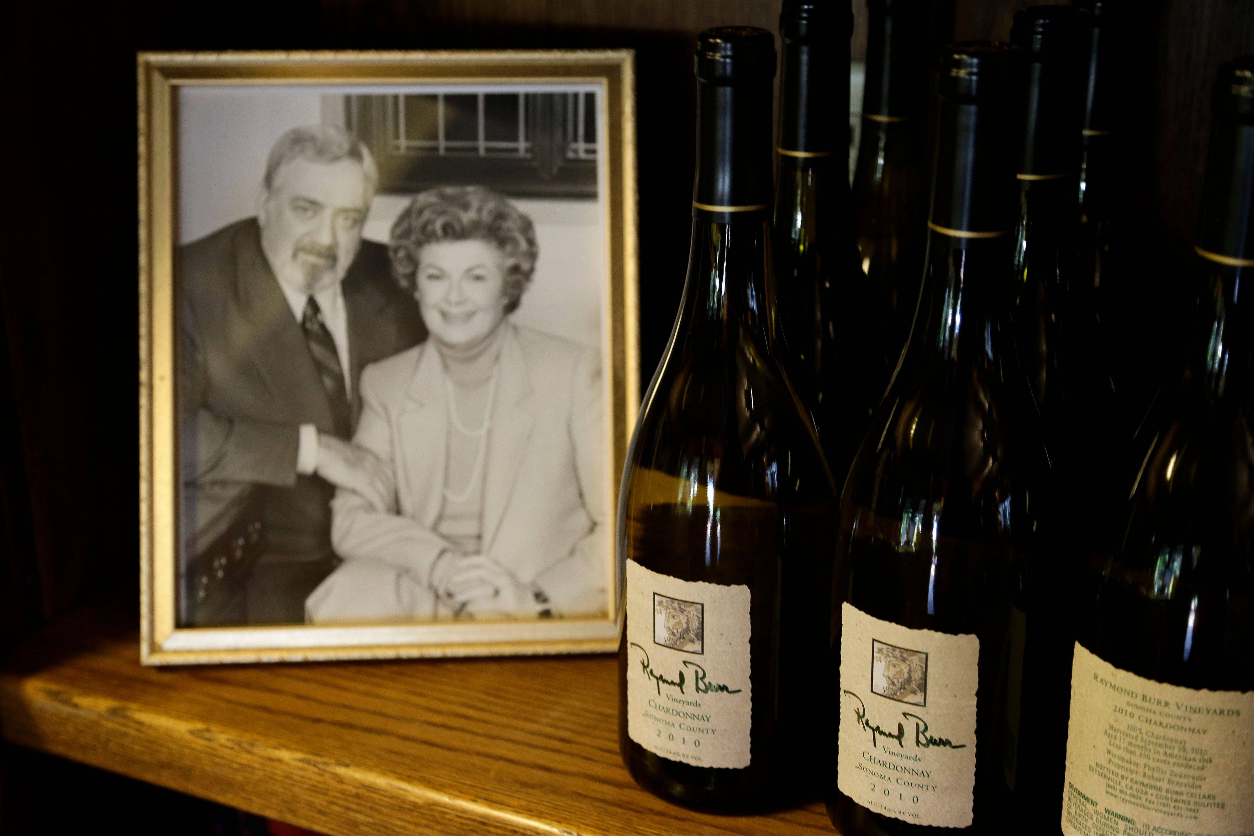 Bottles of chardonnay are shown beside a photograph of the late actor Raymond Burr and actress Barbara Hale at Raymond Burr Vineyards in Healdsburg Calif.