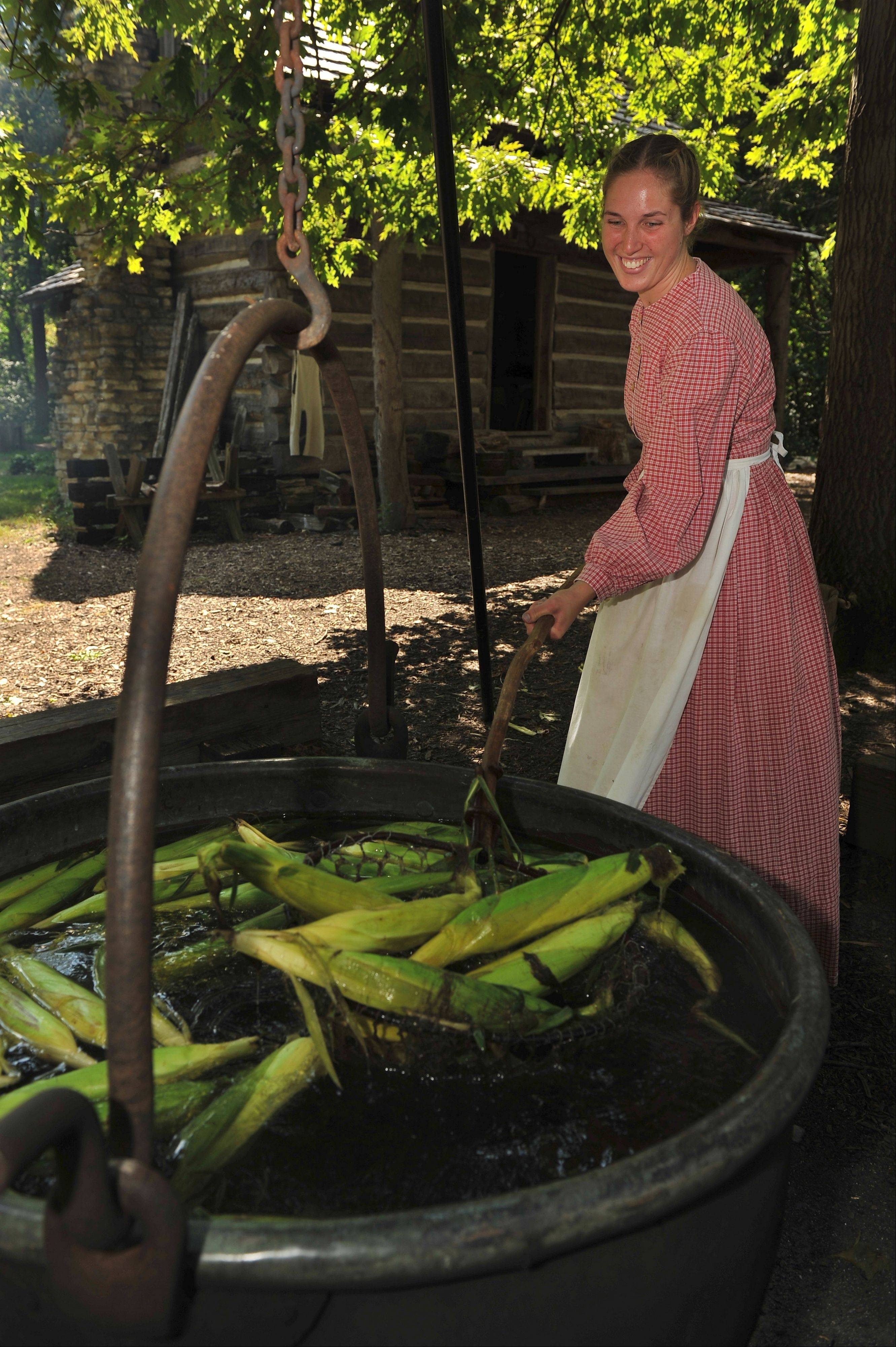 Sarah Vlakancic, a worker at Blackberry Farm, stirs a pot of corn on the farm.