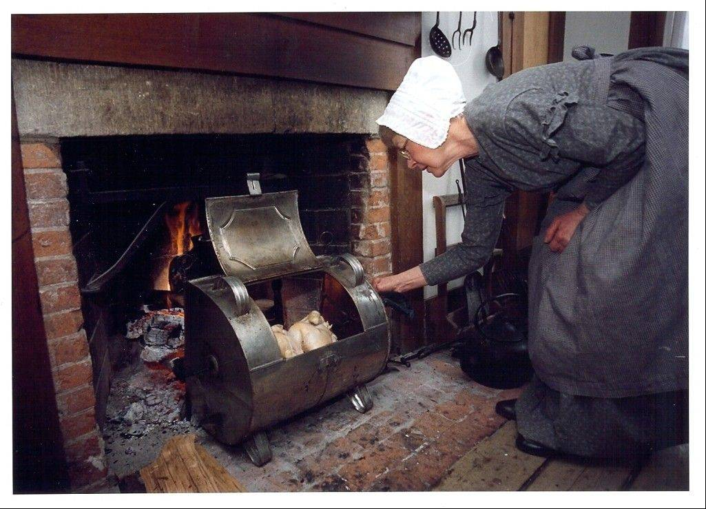 Dressed in the clothing of the day, Linda Saxer, former director and now volunteer, cooks a chicken in Durant House's reflector oven, which worked by capturing radiant heat from the fire and reflecting it toward the food.