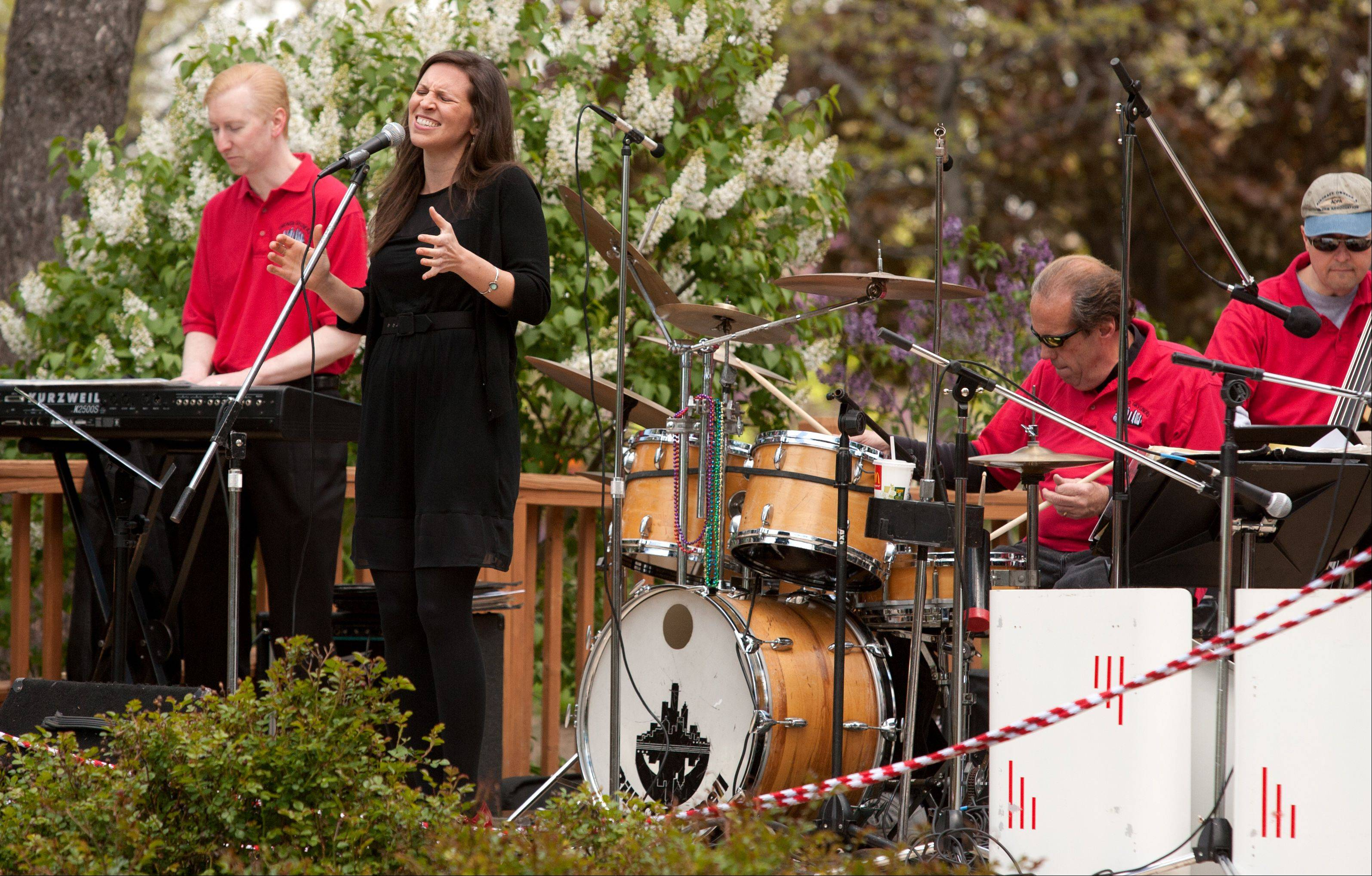 Lead singer Leslie Beukelman, of Bill O'Connell's Chicago Skyliners Big Band, performs at Lilacia Park in Lombard Sunday. O'Connell plays the drums.