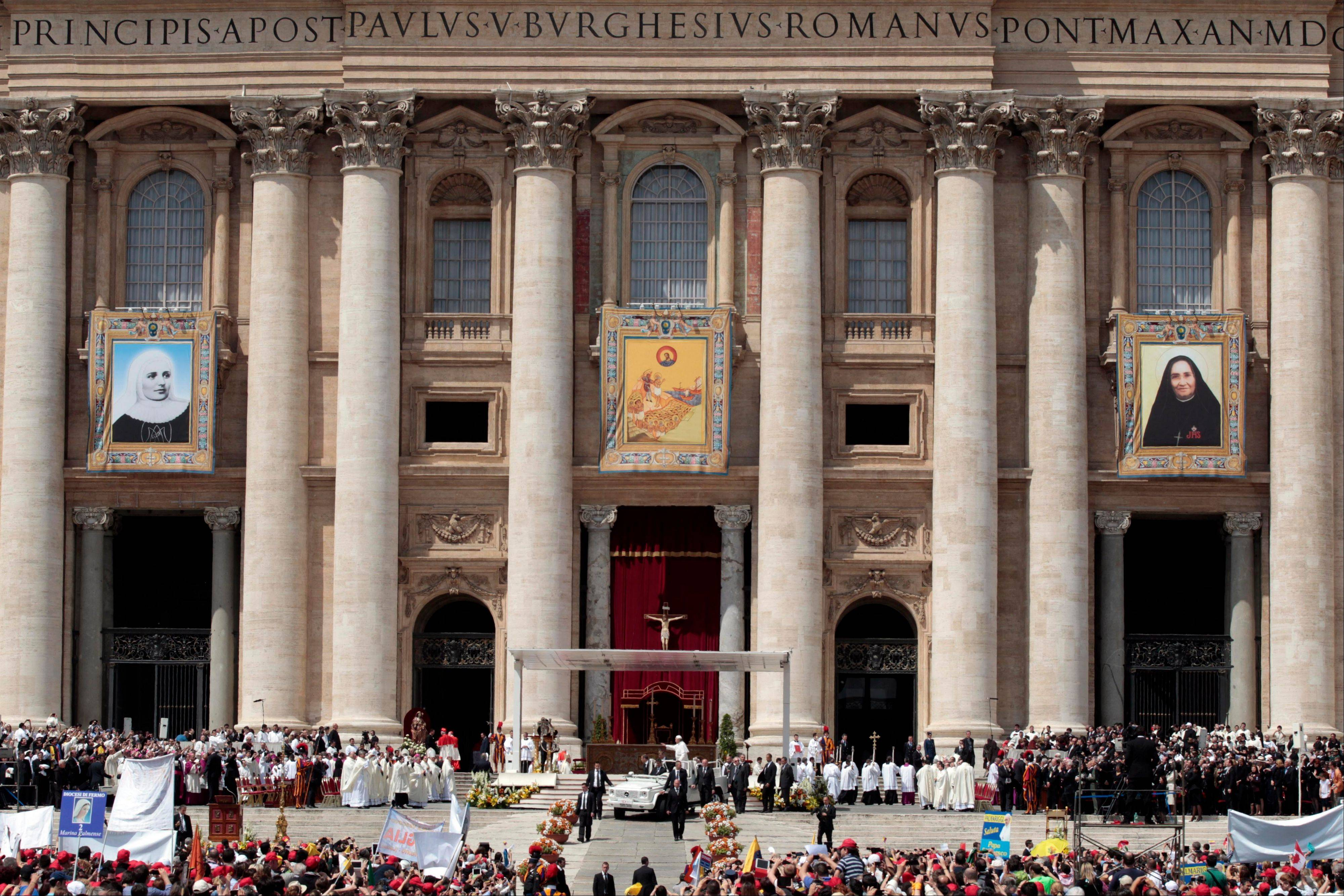 From left, the tapestries of Laura di Santa Caterina da Siena Montoya of Colombia, Antonio Primaldo and his companions, also known as the Martyrs of Otranto, and Maria Guadalupe Garcia Zavala of Mexico, are displayed as Pope Francis, bottom center, leaves at the end of a canonization mass in St. Peter's Square at the Vatican, Sunday