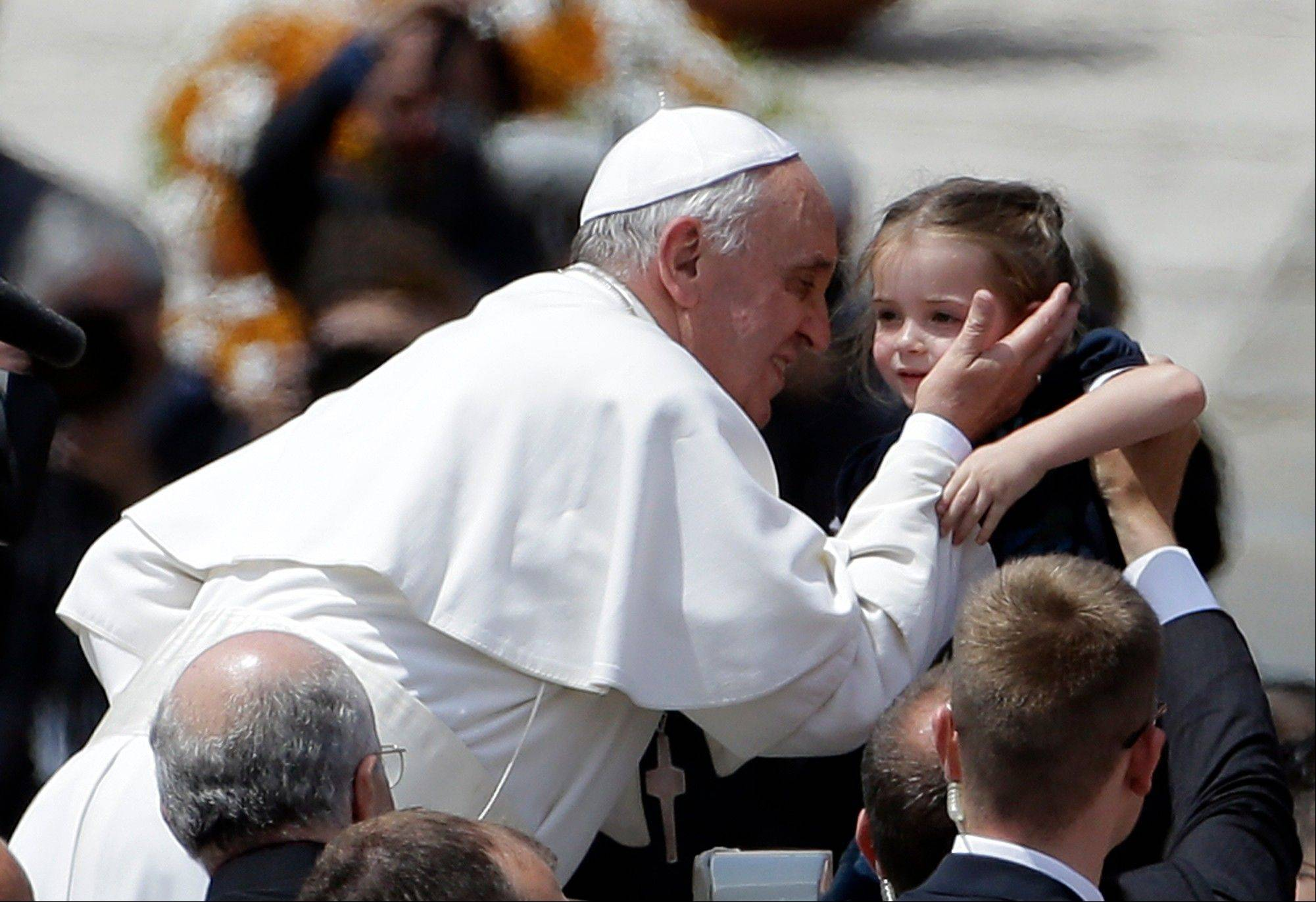Pope Francis kisses a baby at the end of a canonization mass in St. Peter's Square at the Vatican, Sunday.