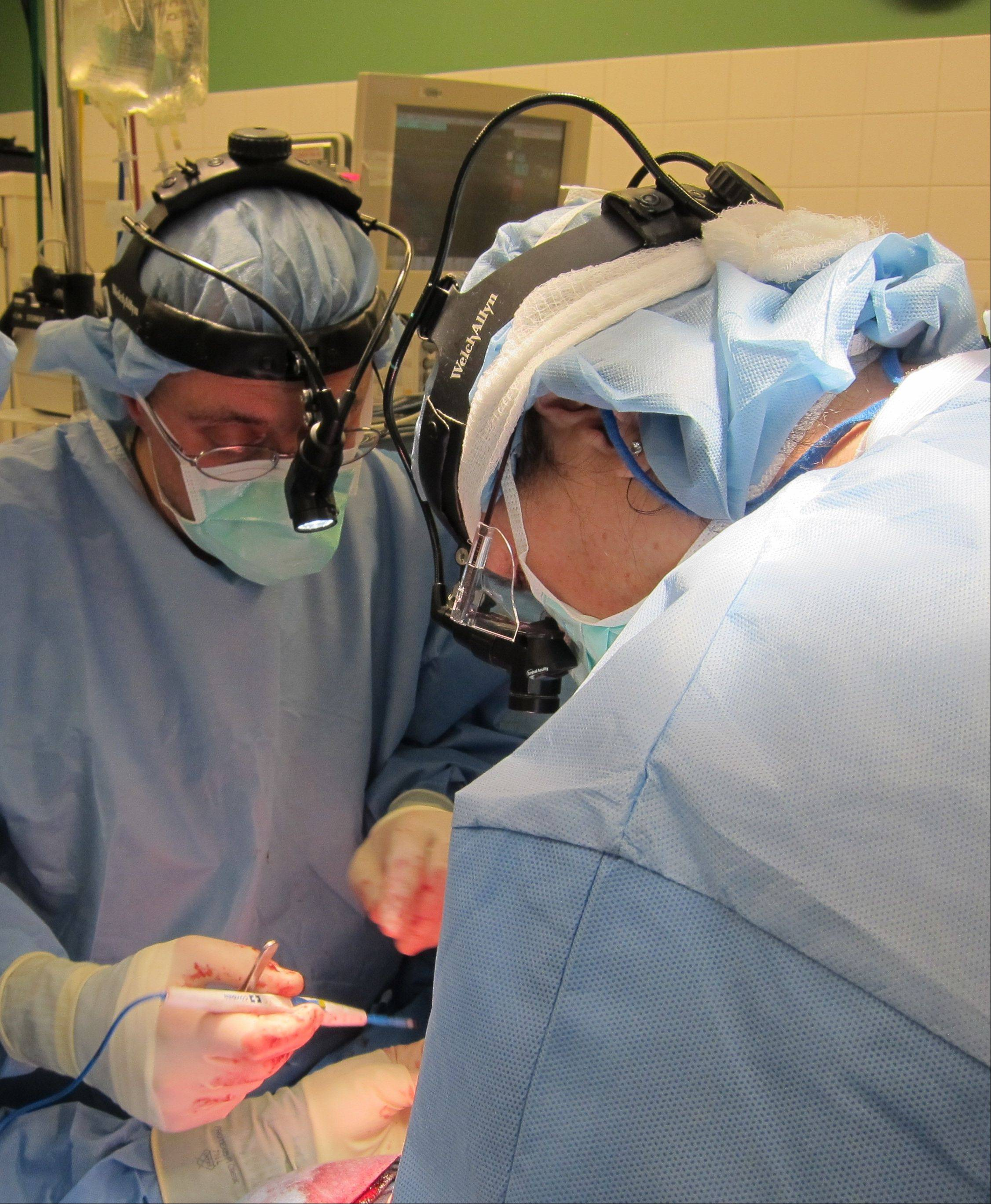 University of Chicago Medicine doctors Fuad Baroody, facing the camera, and Deborah Loeff, right, work to insert a tiny breathing tube down the throat of John Carlos Guzman during a potentially fatal high-tech surgery.