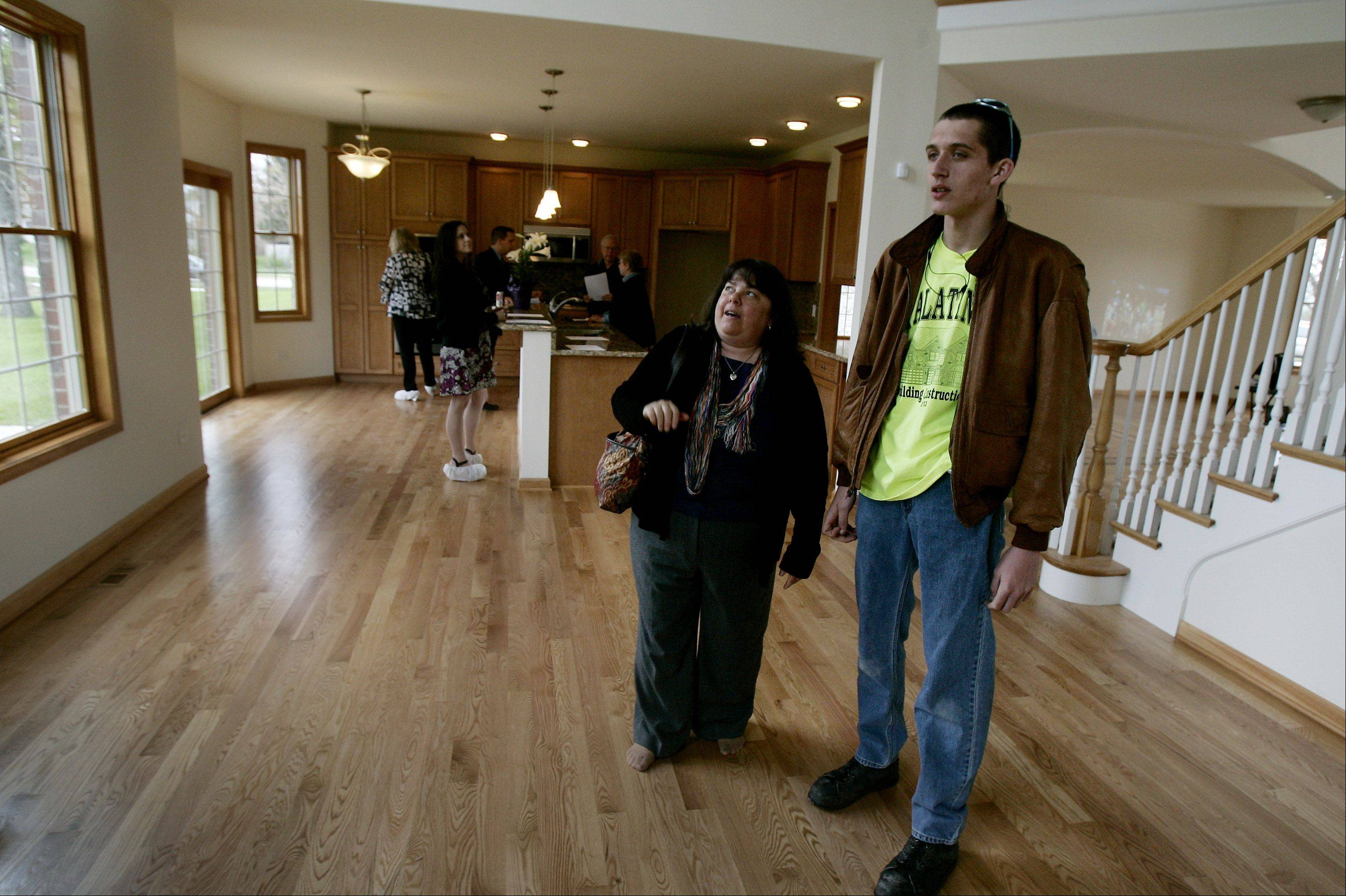Mike Ramser, right, shows his mom, Laura, parts of a living room he helped build during last year's open house at a student-built home on Brockway Street in Palatine. The district will hold another open house this year for three new Palatine houses from 2 to 4 p.m. on Sunday, May 19.