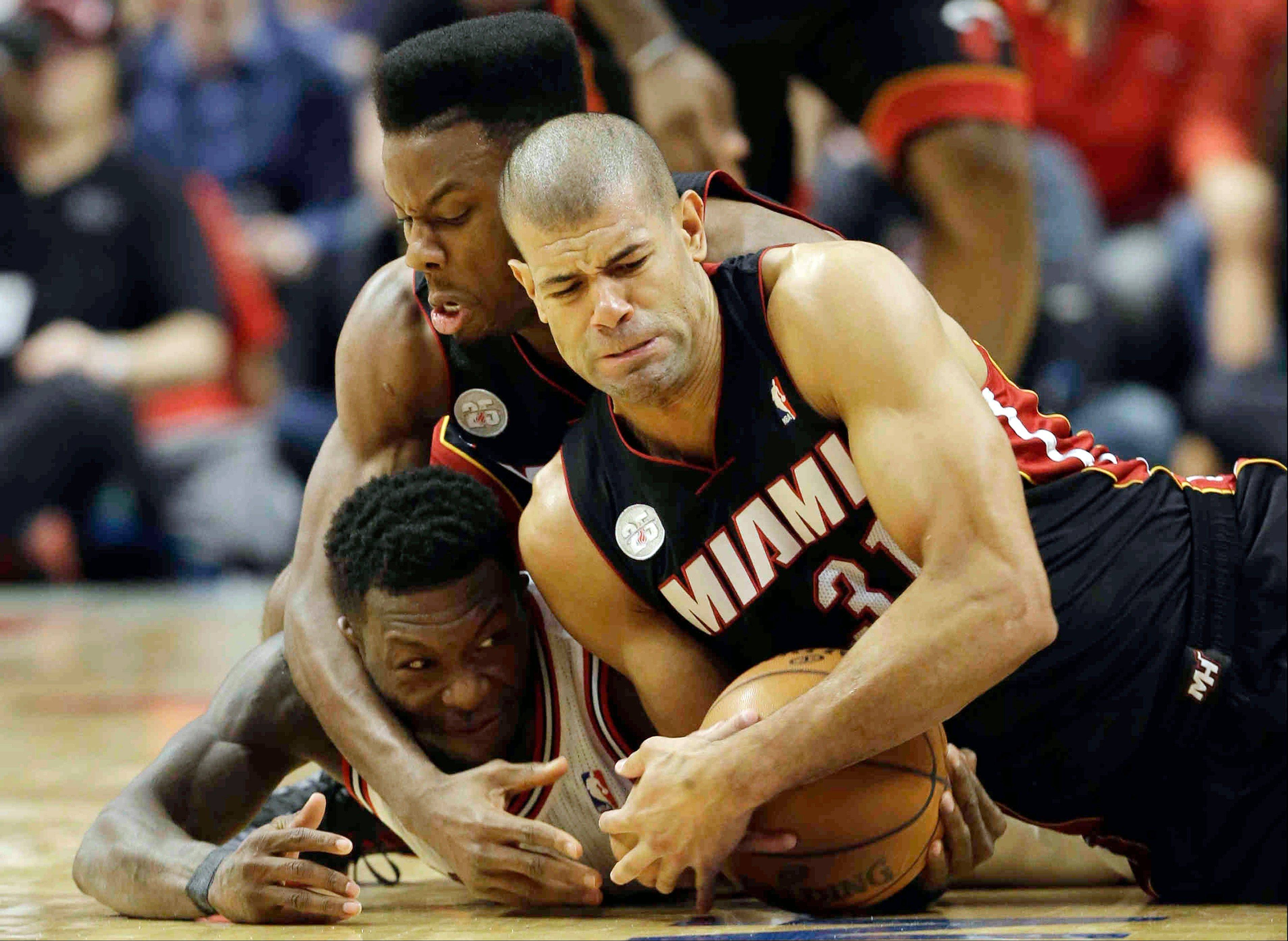 The Bulls' Nate Robinson,left, battles for a loose ball against the Heat's Norris Cole, center, and Shane Battier on Monday at the United Center.