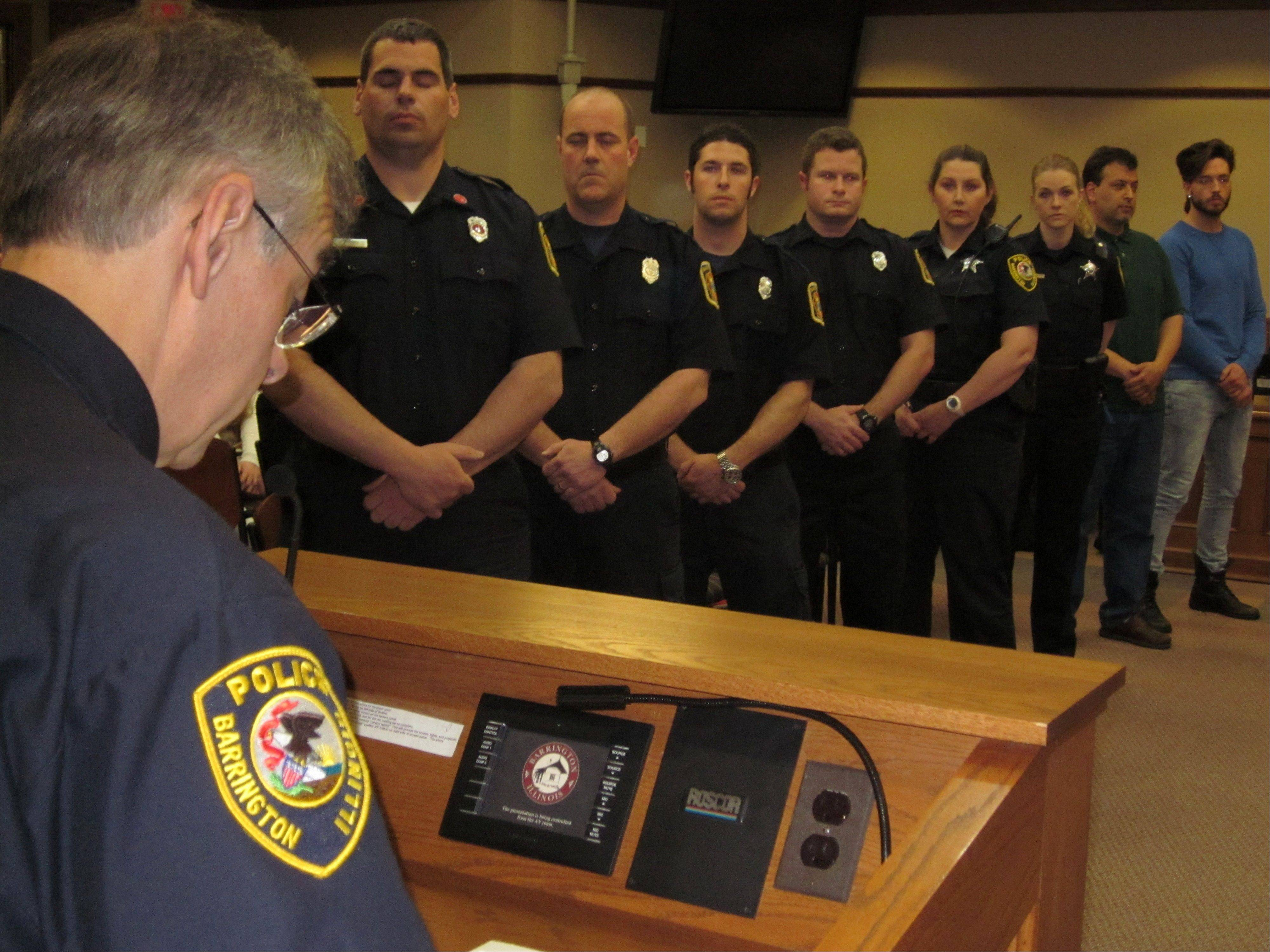 Barrington Police Chief Jerry Libit, left, reads a proclamation honoring the police officers, paramedics and good Samaritans who helped save the life of 11-year-old Dominic Szymanski after the boy was struck by a train March 15, while most of the honorees look on.